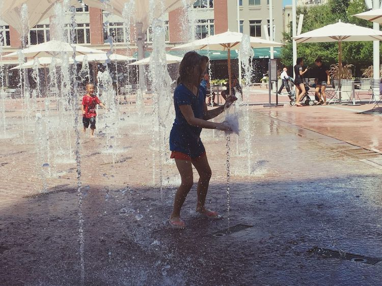 Little girl hitting the fountain stream.. Building Exterior Architecture Lifestyles Leisure Activity Built Structure City Casual Clothing Happiness Fort Worth Stockyards City Life Person Outdoors Day In Front Of Focus On Foreground Vacations