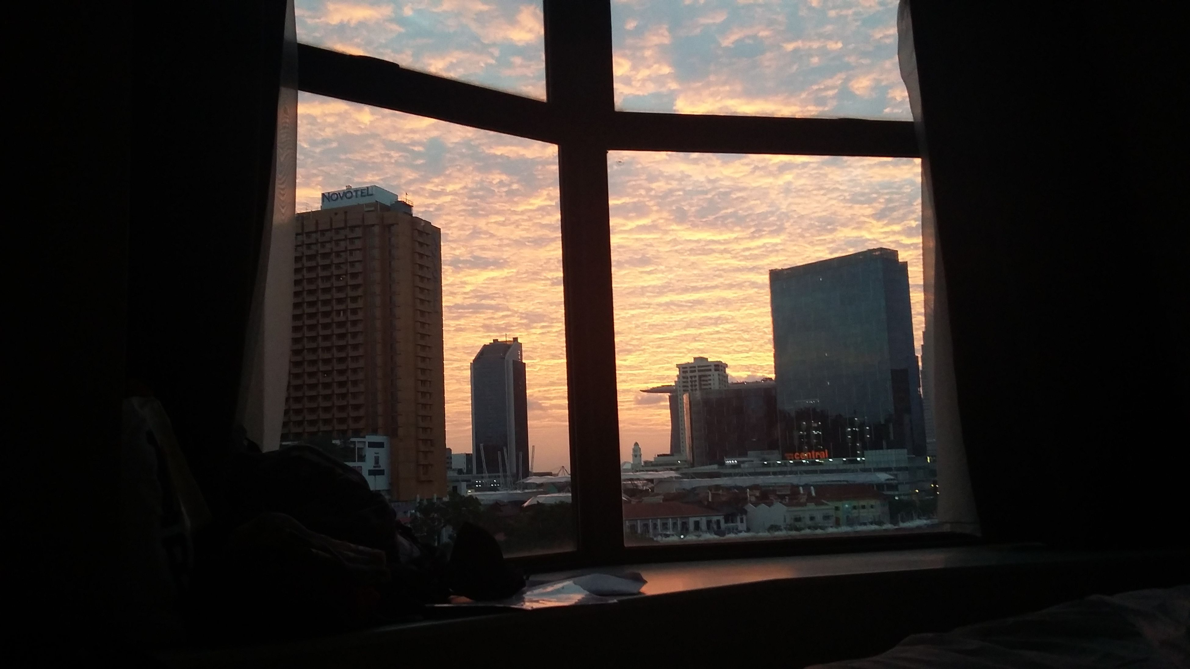 window, indoors, architecture, built structure, glass - material, building exterior, silhouette, city, sky, skyscraper, transparent, looking through window, modern, cityscape, office building, sunset, cloud - sky, sitting, dark, tower