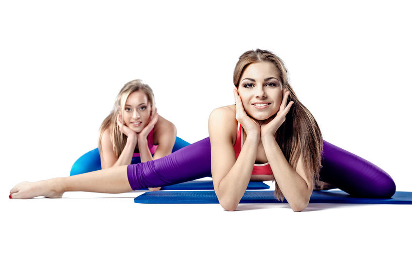 Two beautiful young woman doing stretching exercise Athlete Athletic Exercising Females Looking At Camera Stretching Legs Woman Beautiful Woman Blond Hair Brunette Fitness Fitness Training Girls Healthy Lifestyle Smiling Sport Sportive Stretching Studio Shot Two People Wellbeing Women Workout Young Adult Young Women