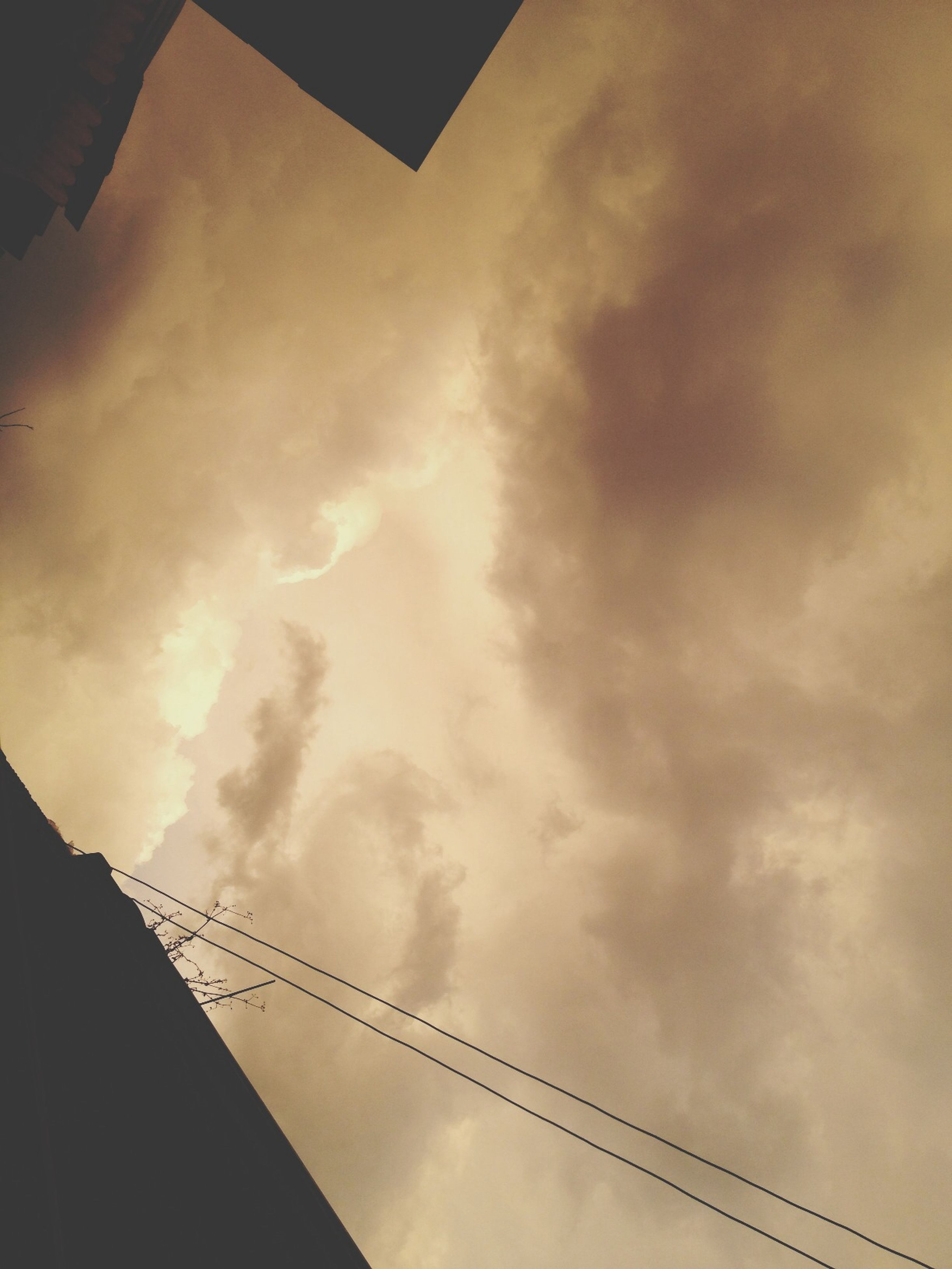 low angle view, sky, cloud - sky, architecture, built structure, sunset, cloudy, building exterior, silhouette, cloud, high section, outdoors, no people, connection, dusk, building, nature, orange color, city, cable