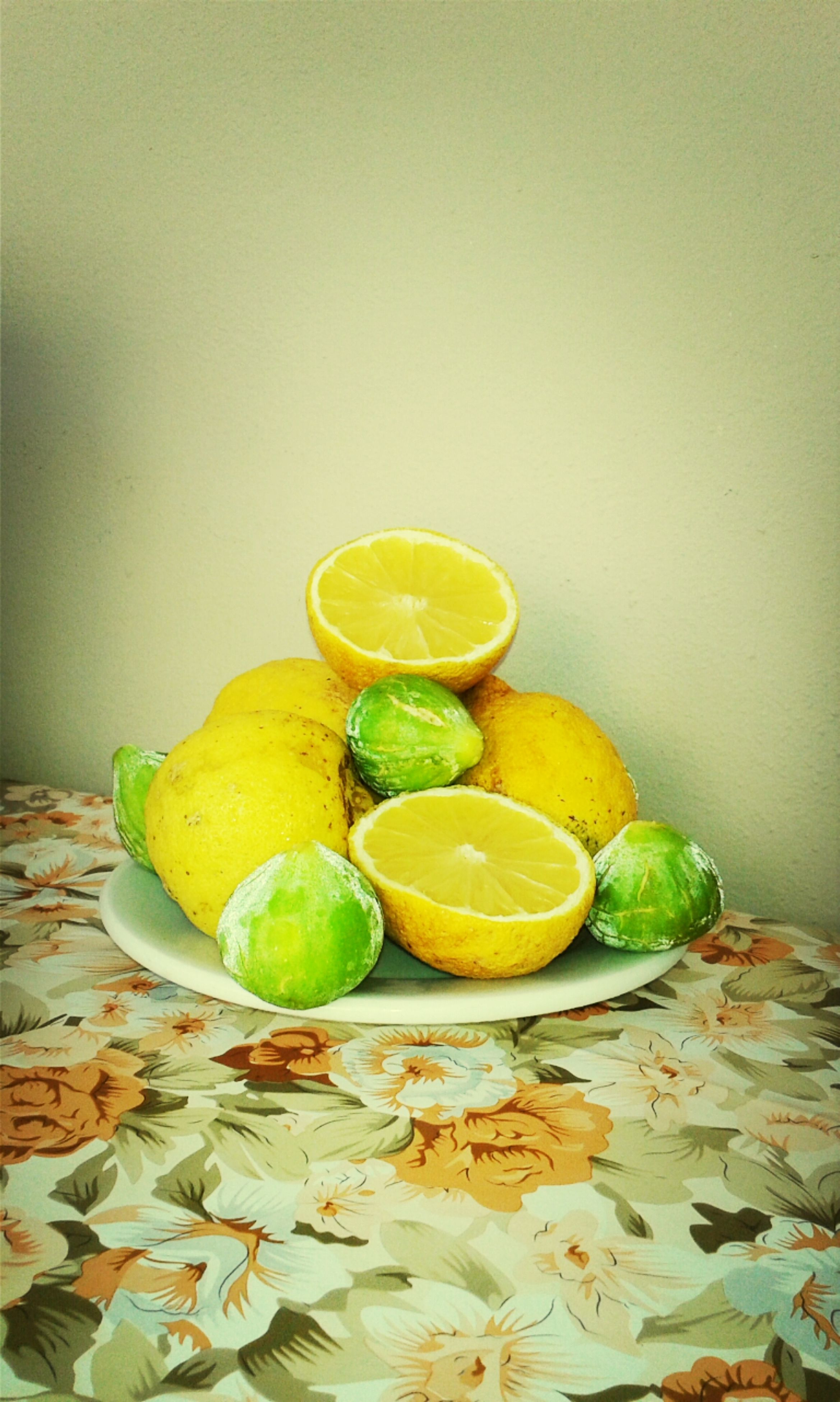 fruit, food and drink, yellow, indoors, food, freshness, still life, healthy eating, green color, table, leaf, close-up, wall - building feature, copy space, no people, lemon, home interior, orange - fruit, grape, organic