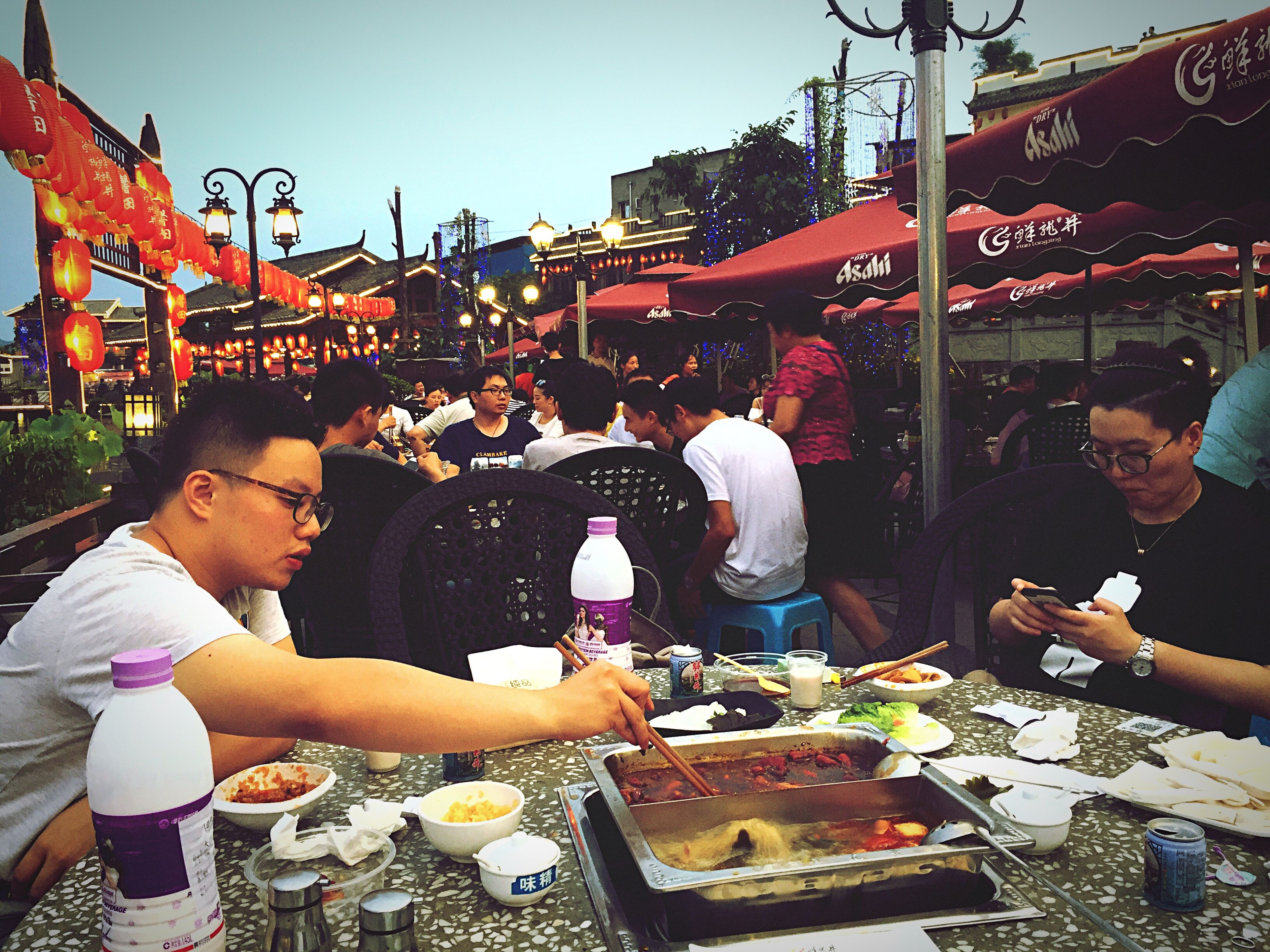 real people, food, food and drink, outdoors, eating, day, large group of people, market, men, lifestyles, people in the background, togetherness, healthy eating, building exterior, city, freshness, architecture, people