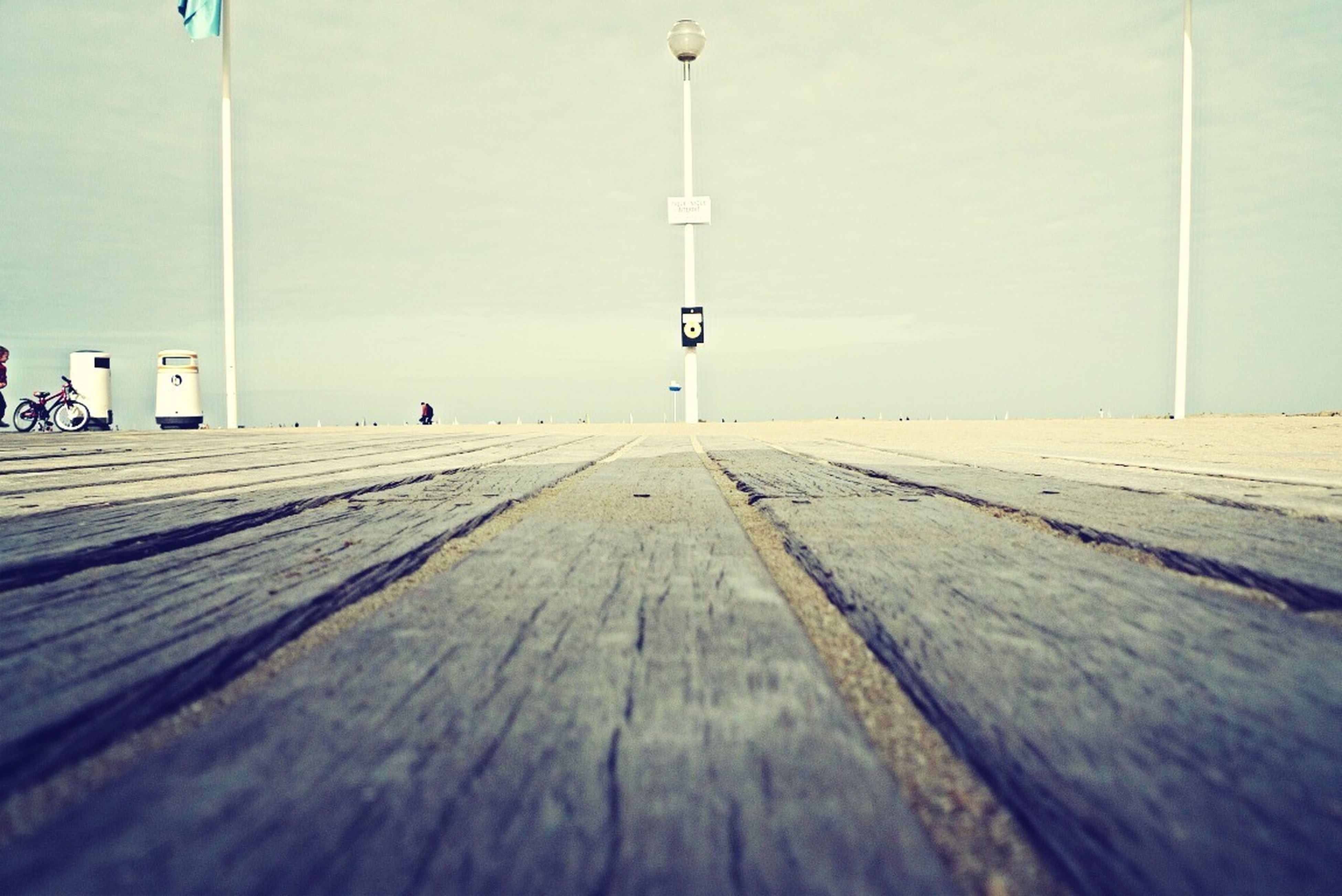 the way forward, built structure, diminishing perspective, architecture, wood - material, vanishing point, sky, day, walkway, surface level, building exterior, long, empty, boardwalk, outdoors, pole, street light, in a row, incidental people, railing