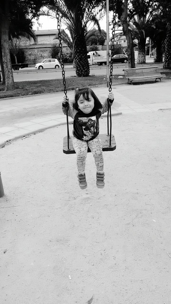 childhood, playground, tree, outdoor play equipment, swing, elementary age, day, outdoors, full length, real people, park - man made space, playing, rope swing, architecture, one person, people