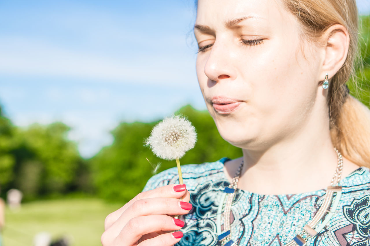 one person, outdoors, headshot, focus on foreground, day, front view, young women, real people, young adult, leisure activity, nature, close-up, beautiful woman, blond hair, sky, flower, people