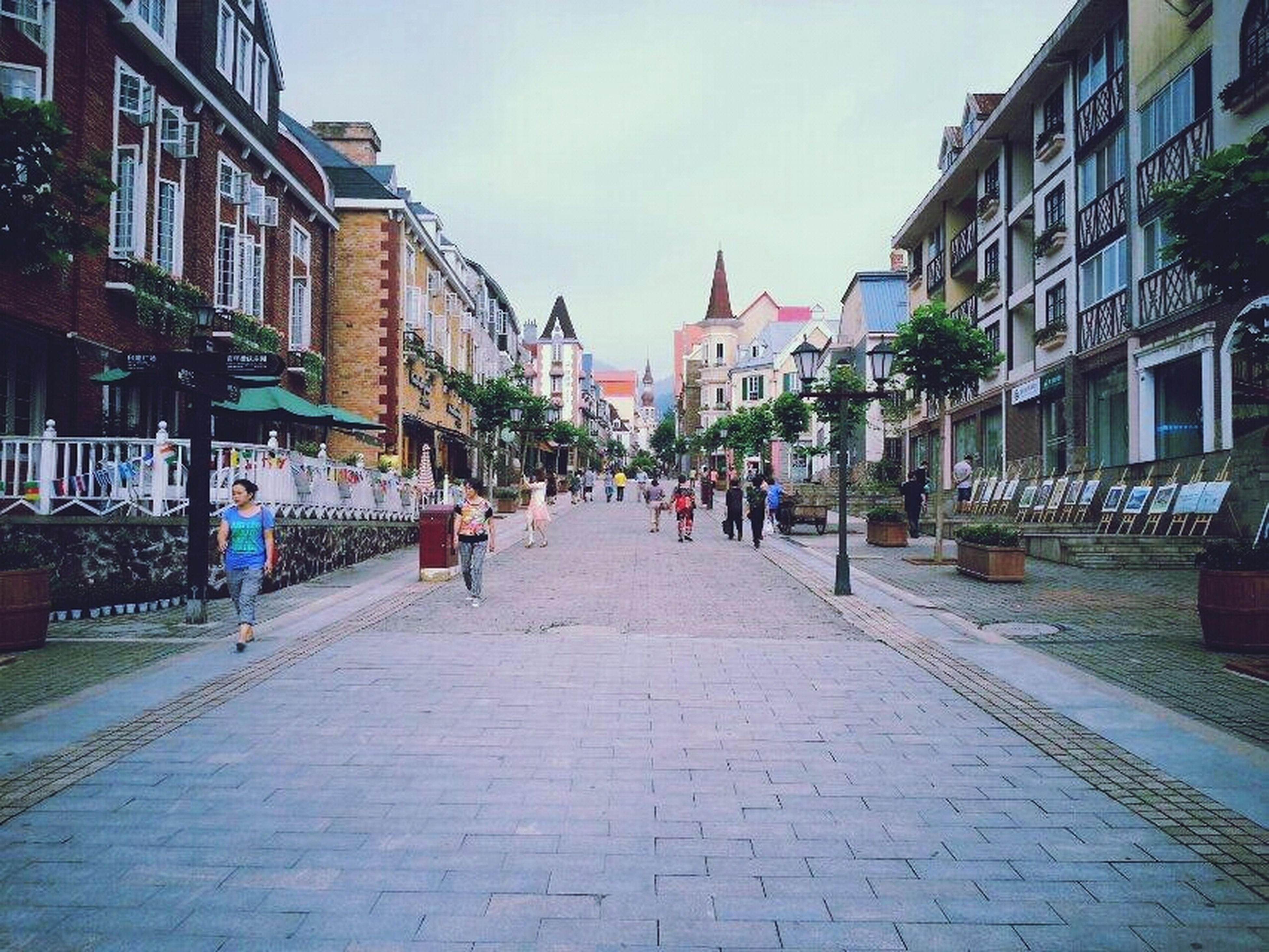 building exterior, architecture, built structure, street, the way forward, city, sky, cobblestone, residential building, diminishing perspective, residential structure, incidental people, building, day, city life, outdoors, road, street light, vanishing point, old town