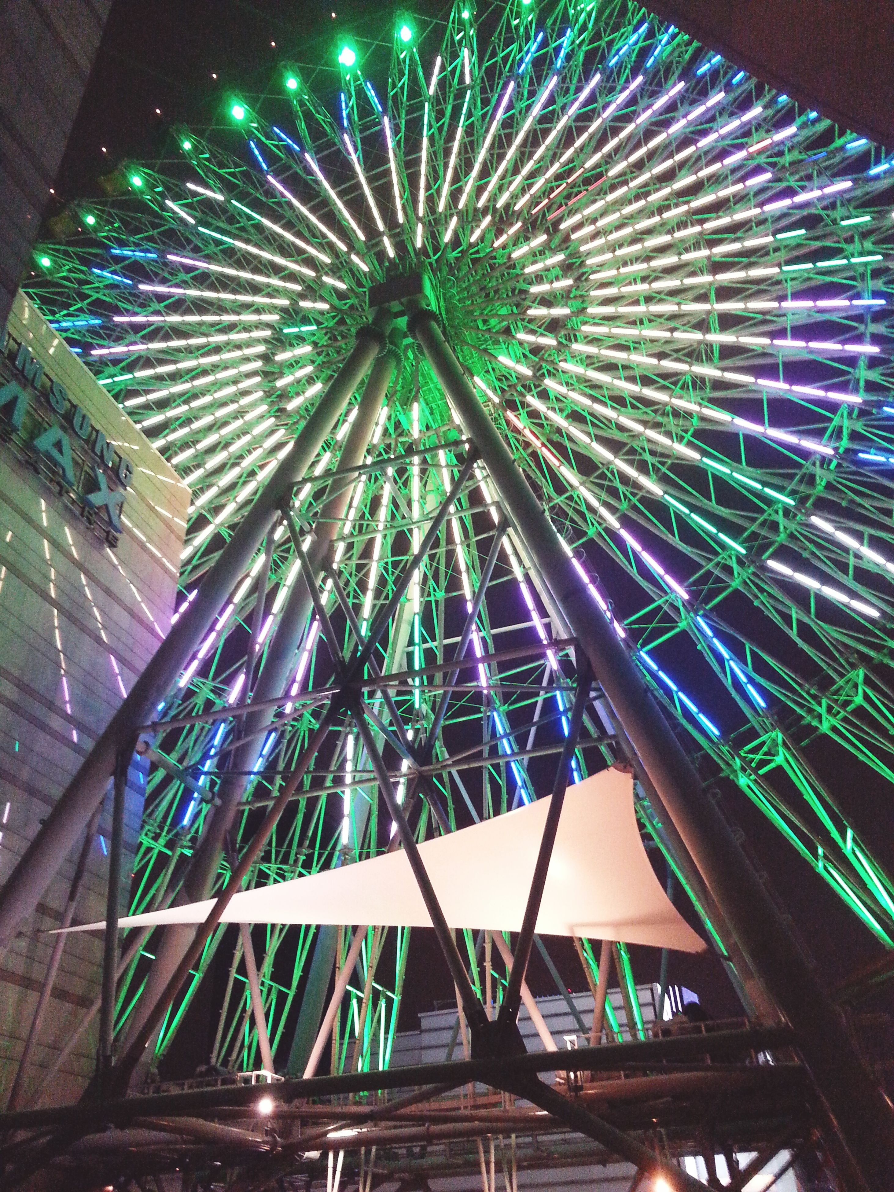 low angle view, built structure, architecture, illuminated, building exterior, indoors, arts culture and entertainment, ceiling, night, no people, modern, pattern, architectural feature, sky, ferris wheel, lighting equipment, glass - material, decoration, amusement park