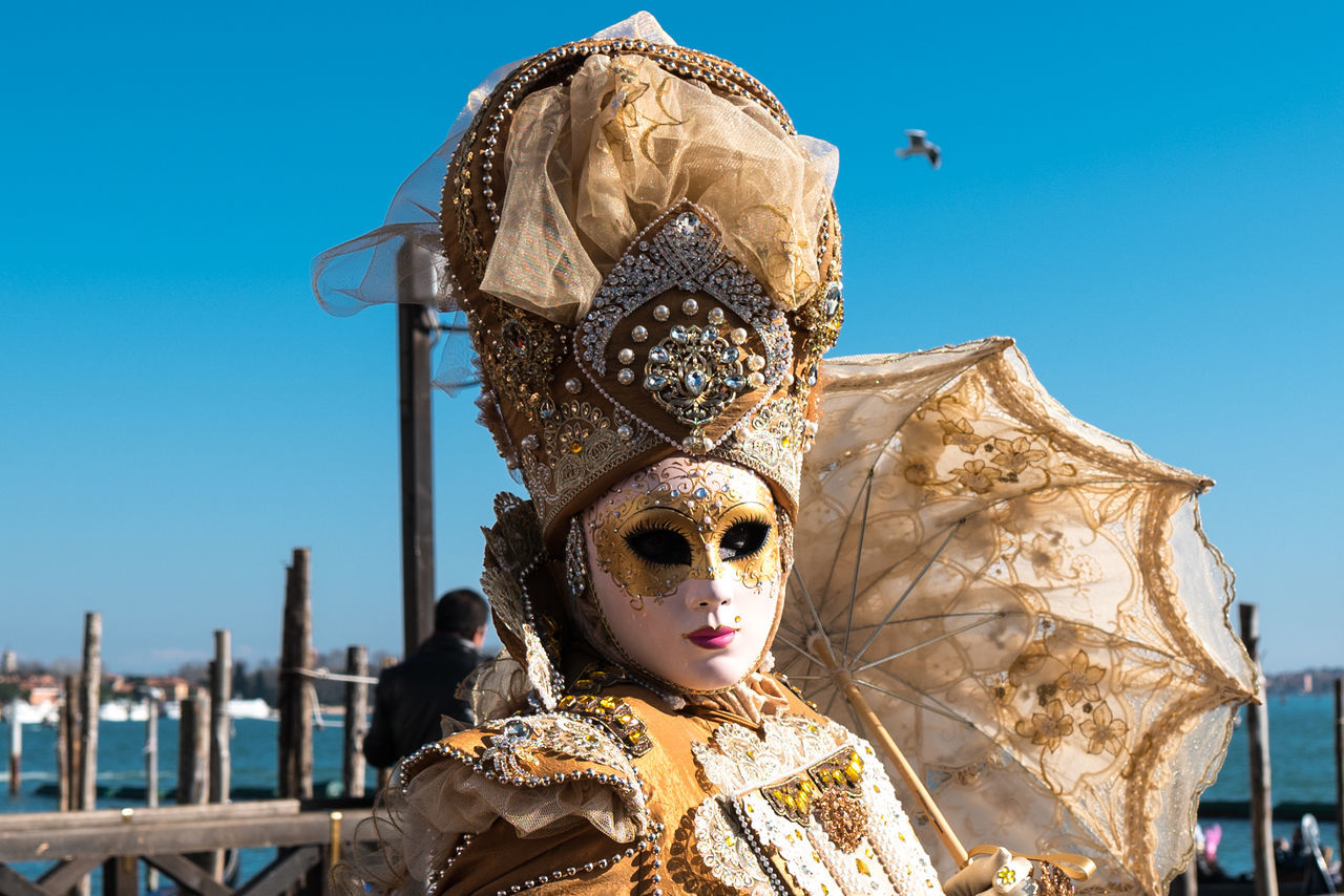 mask - disguise, venetian mask, day, outdoors, tradition, focus on foreground, blue, sunlight, arts culture and entertainment, clear sky, real people, sky, close-up, one person