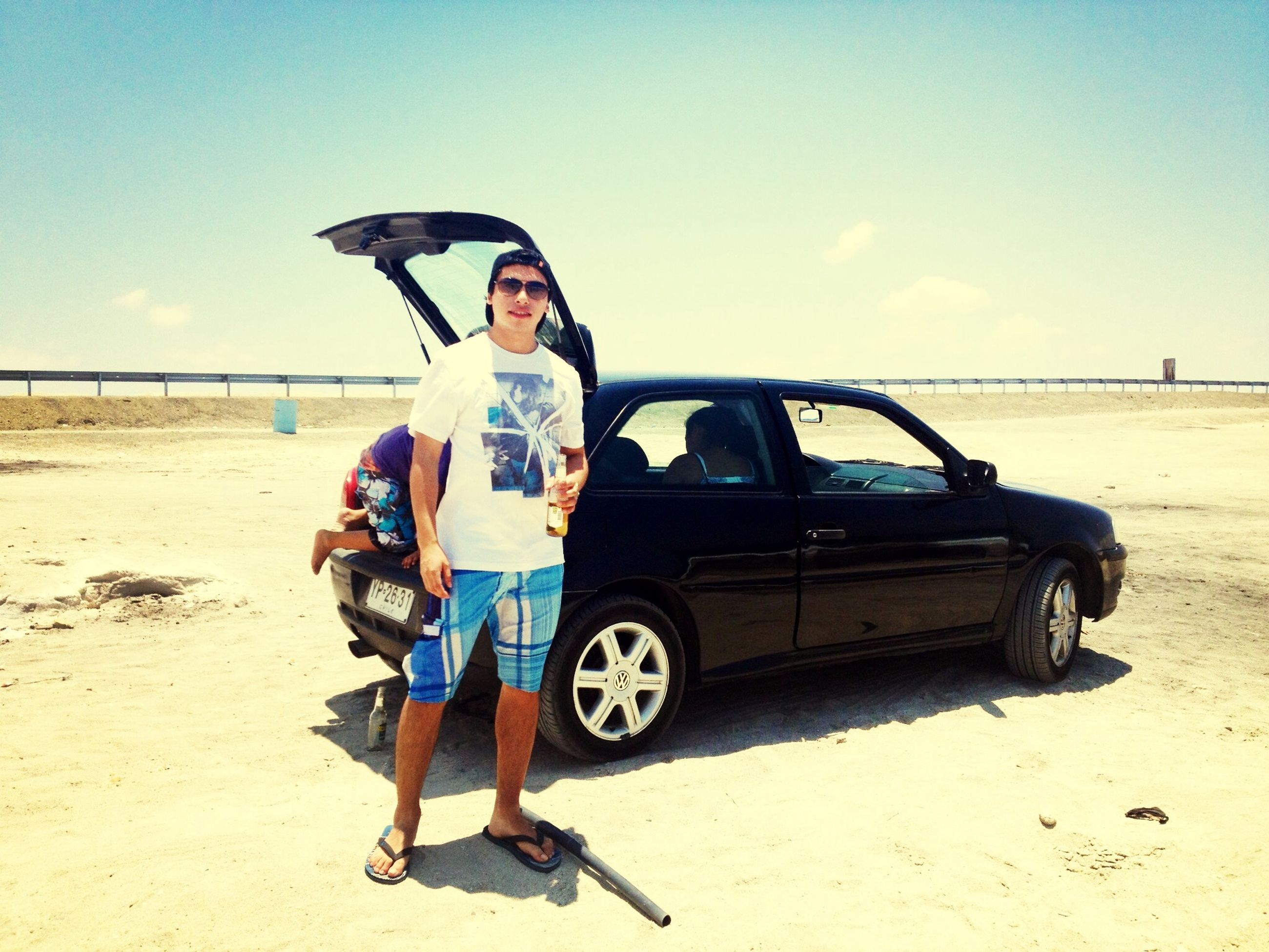 sand, beach, full length, lifestyles, leisure activity, casual clothing, shore, sky, person, sea, young adult, sunlight, transportation, land vehicle, mode of transport, sunglasses, travel, vacations
