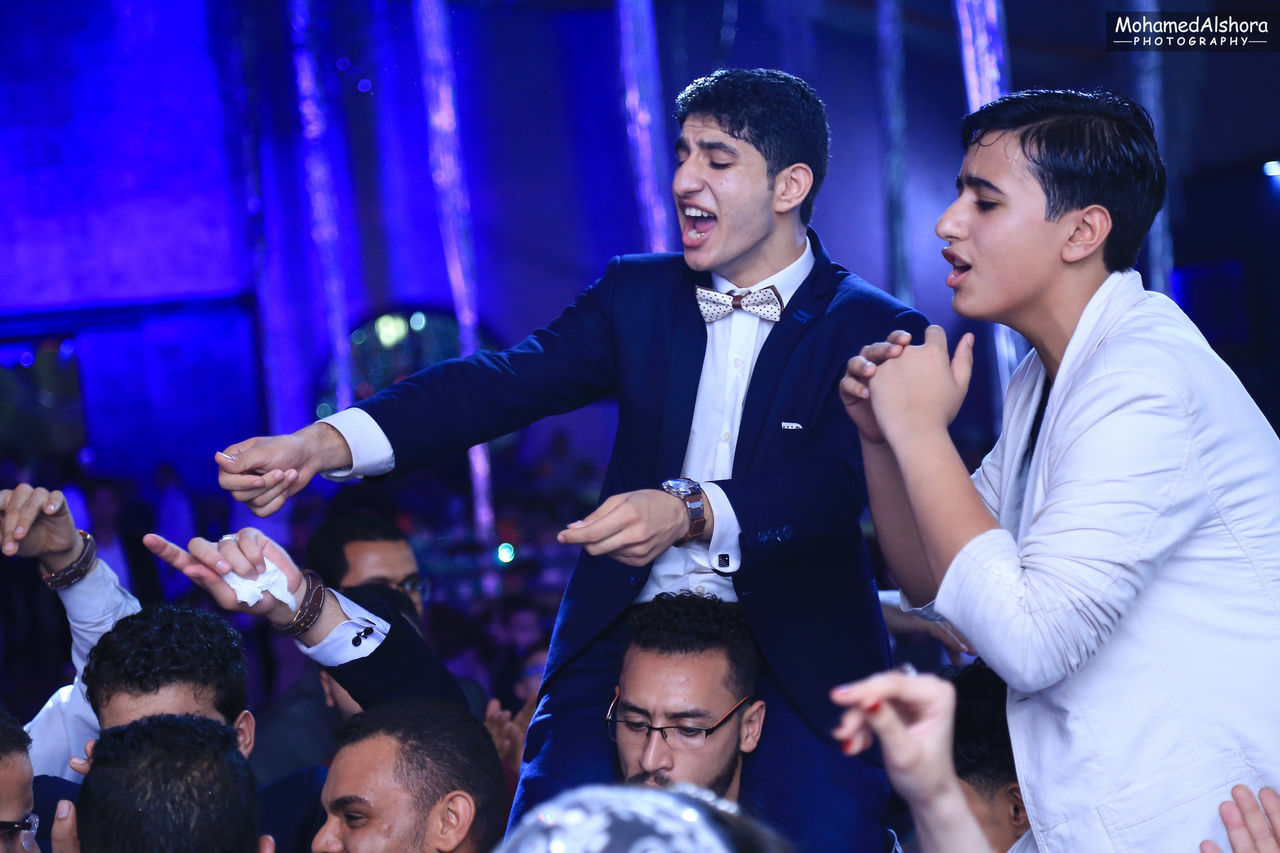 Adult Arms Raised Arts Culture And Entertainment Carefree Cheerful Enjoyment Fashion Formalwear Friendship Front View Indoors  Leisure Activity Lifestyles Men Microphone Music Night Nightclub Nightlife People Smiling Waist Up Well-dressed Women Young Adult