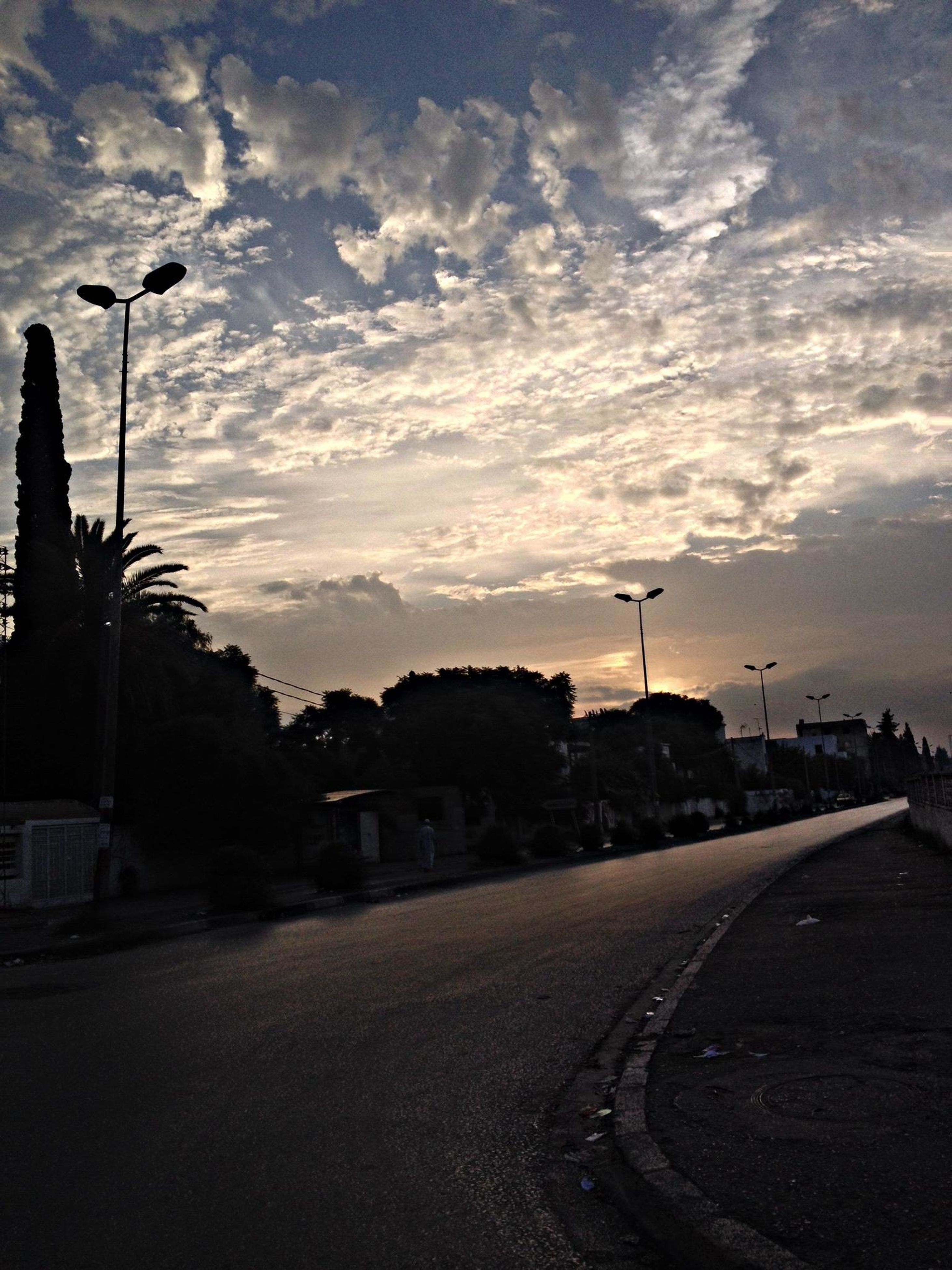 sky, the way forward, road, building exterior, street light, street, cloud - sky, architecture, built structure, silhouette, sunset, cloudy, transportation, cloud, diminishing perspective, tree, road marking, vanishing point, empty road, empty