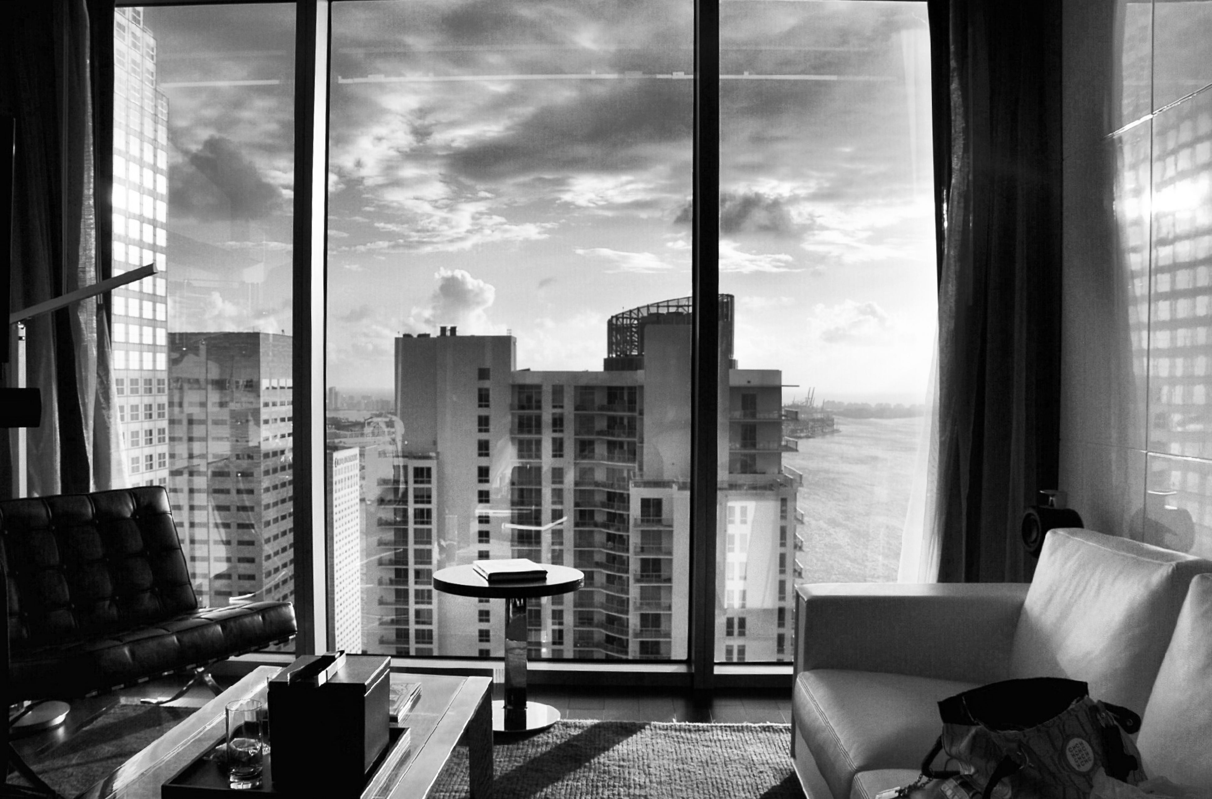 window, indoors, architecture, glass - material, chair, built structure, table, sky, transparent, absence, sea, building exterior, day, empty, sunlight, cloud - sky, city, horizon over water, no people, restaurant