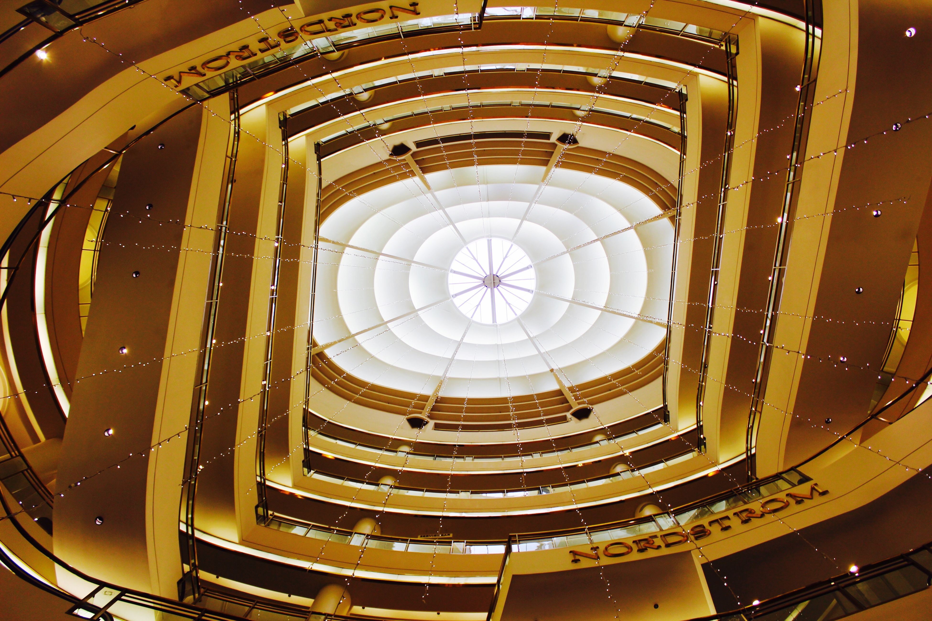 indoors, architecture, built structure, ceiling, low angle view, illuminated, circle, pattern, architectural feature, design, directly below, skylight, modern, geometric shape, no people, glass - material, interior, arch, building, clock