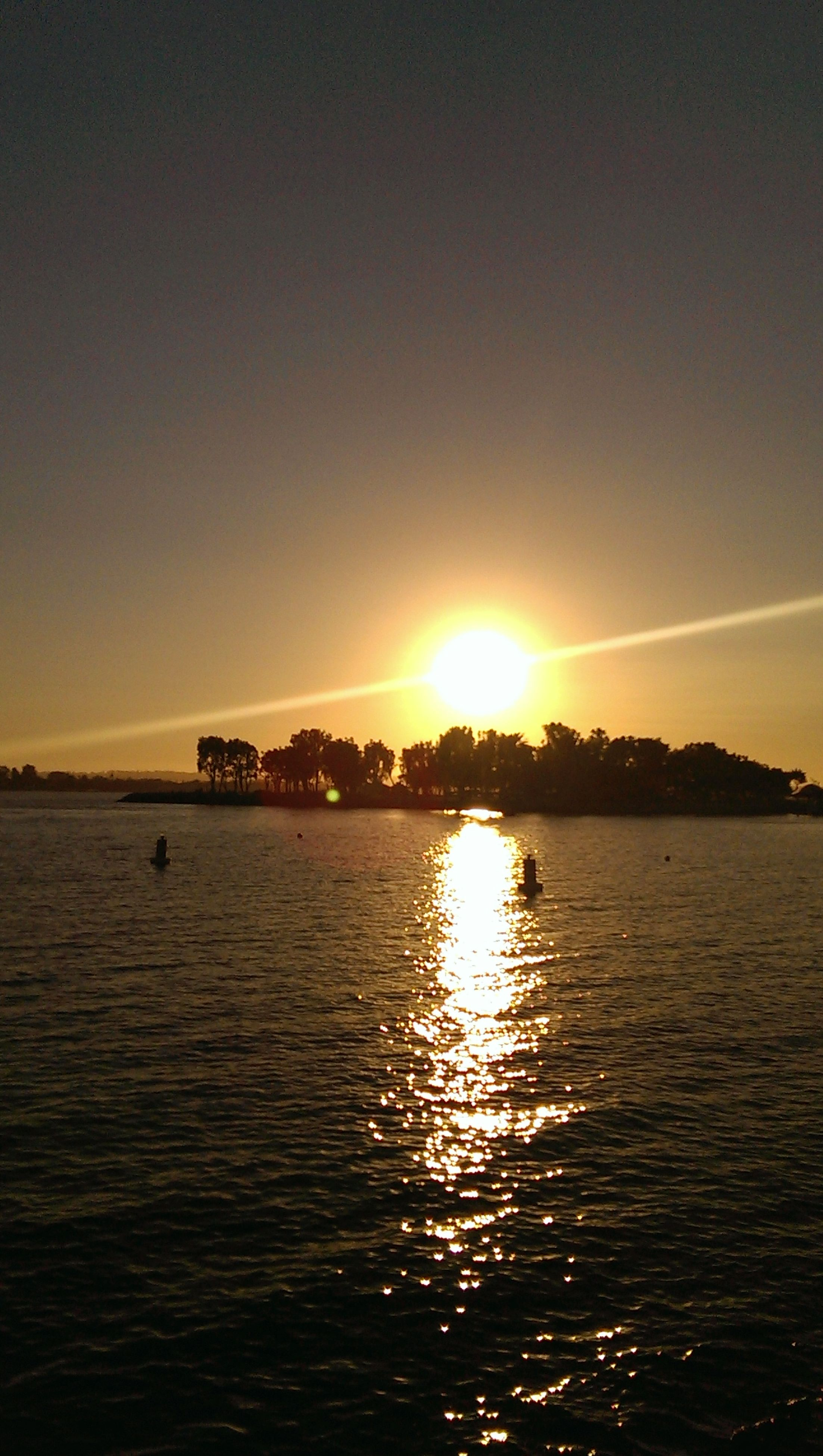 sunset, sun, water, waterfront, sea, orange color, scenics, tranquil scene, beauty in nature, tranquility, reflection, sunlight, rippled, sky, idyllic, nature, silhouette, lens flare, sunbeam, outdoors