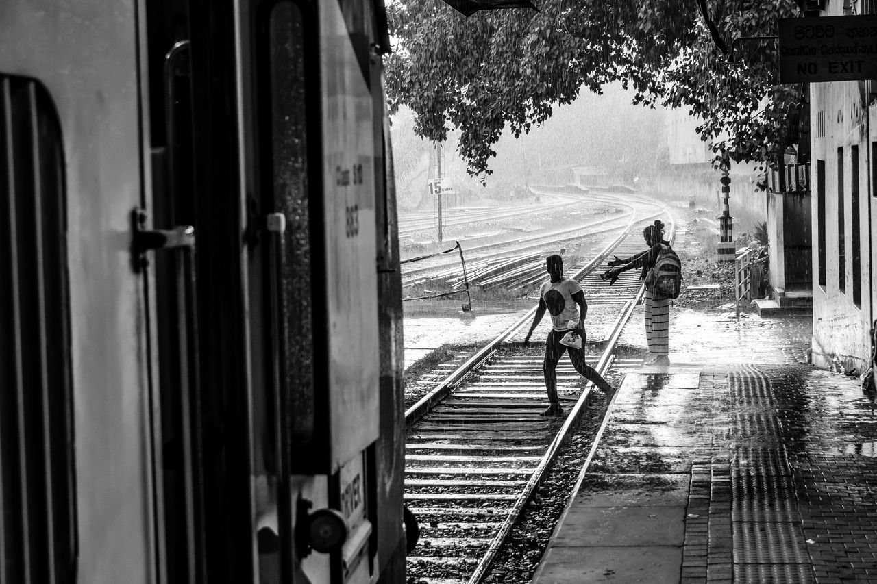Adult Black And White Couple Day Full Length Land Vehicle Men Mode Of Transport Monochrome Nature Outdoors People Public Transportation Rail Transportation Railroad Track Rain Raining Real People Sri Lanka Train Train Station Transportation Tree Two People Walking