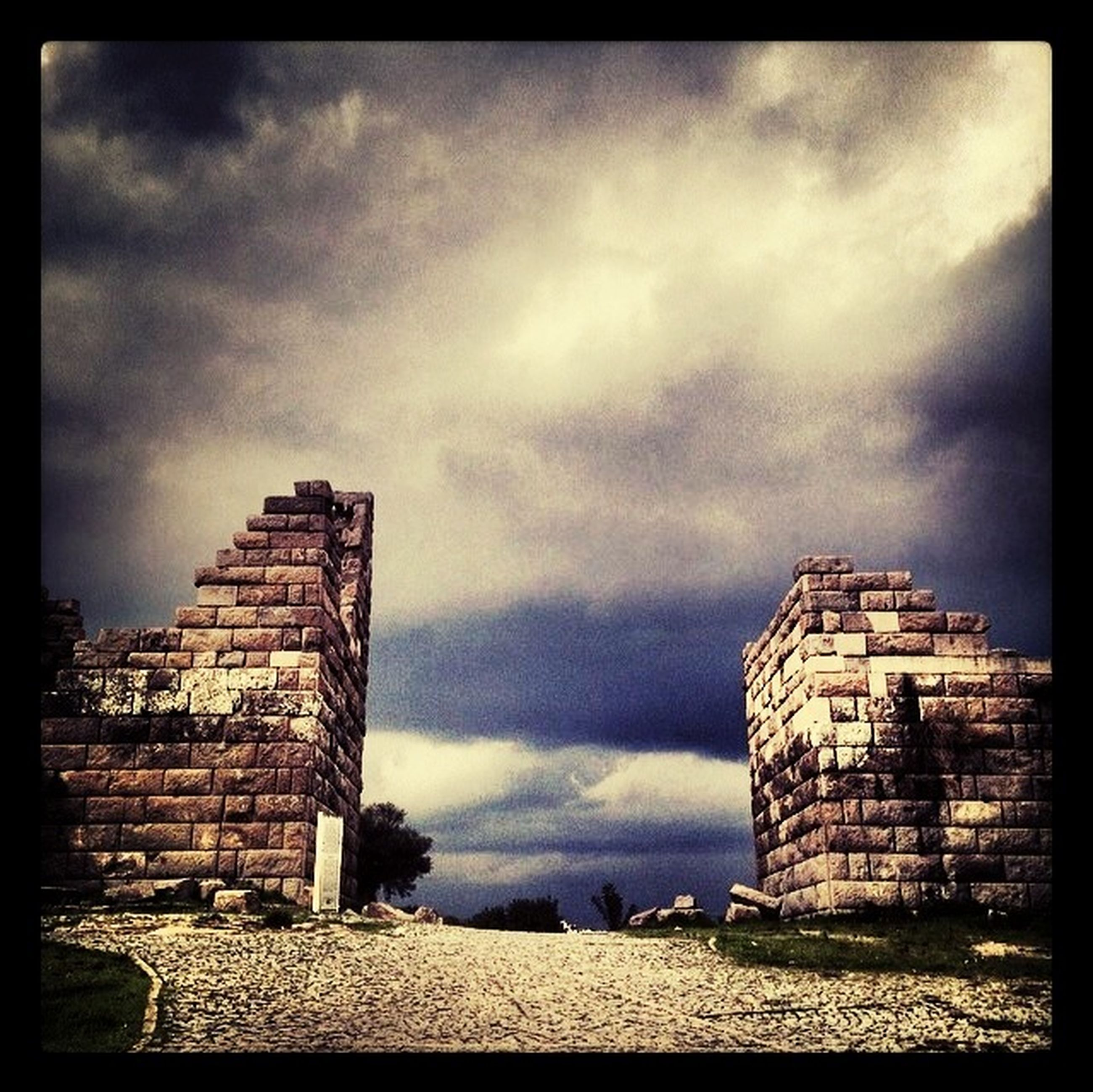 architecture, built structure, building exterior, sky, cloud - sky, cloudy, abandoned, damaged, old, obsolete, run-down, deterioration, auto post production filter, old ruin, ruined, cloud, weathered, history, low angle view, stone wall