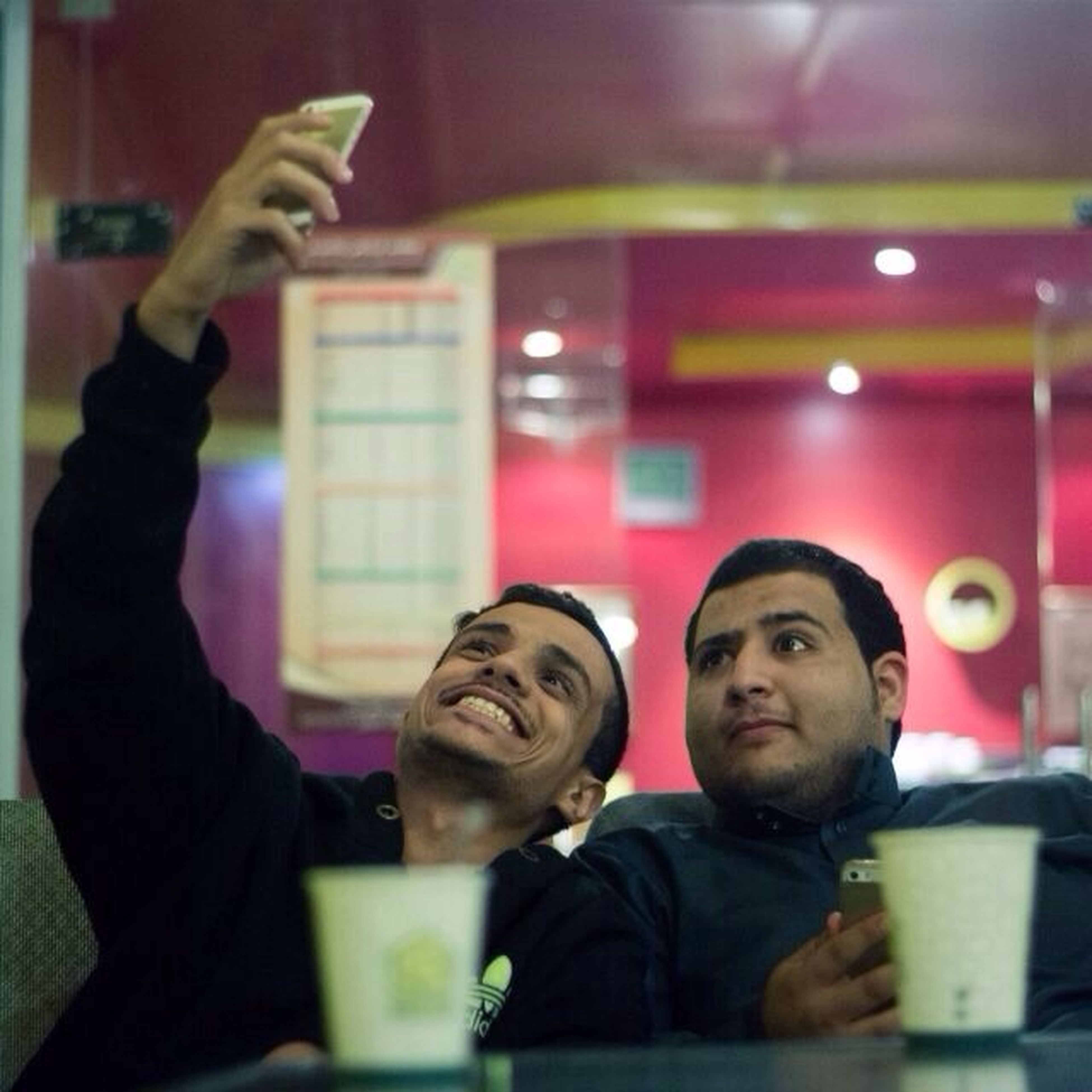 indoors, lifestyles, togetherness, leisure activity, casual clothing, bonding, person, boys, young men, illuminated, love, childhood, technology, holding, photographing, three quarter length, waist up