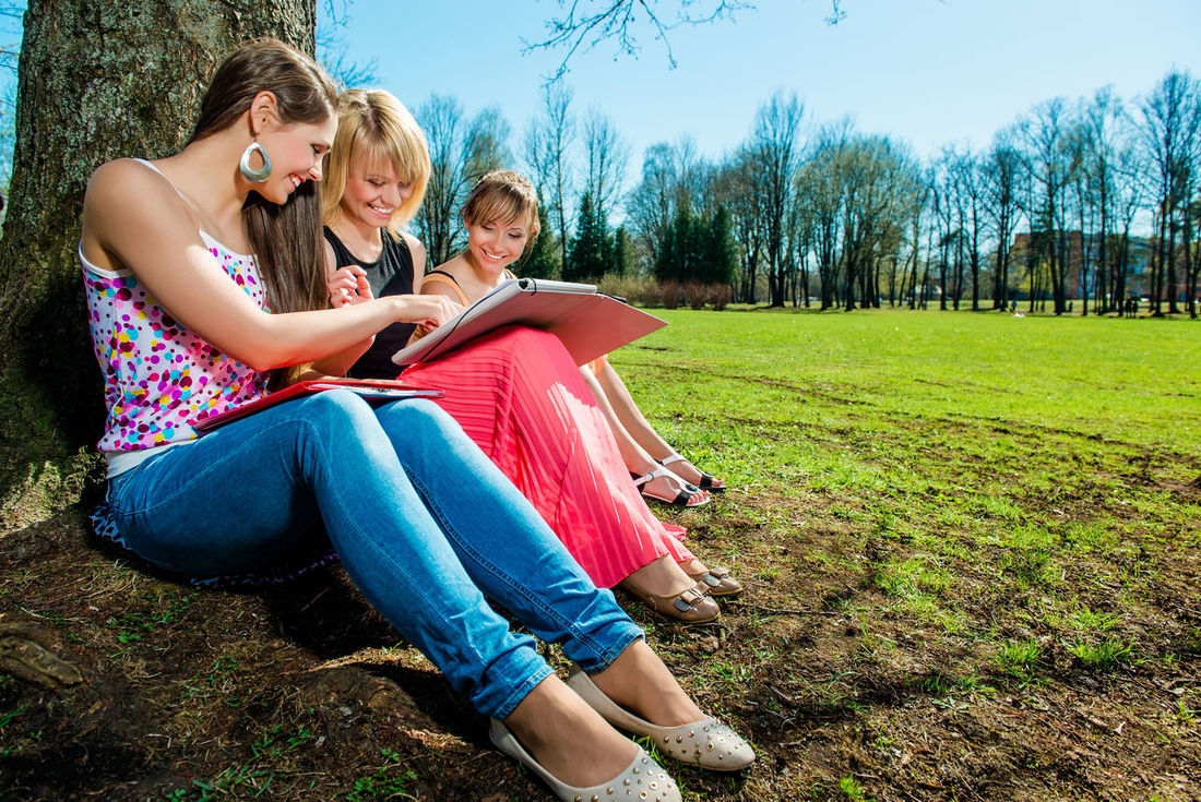 Group of students studying outdoors Bright Colors Friends Happy Students Summertime Trees Cheerful Day Friendship Full Length Girls Grass Outdoors Park - Man Made Space People Sitting Spring Springtime Styding Summer Sunny Day Teenage Girls Teenager Togetherness Young Adult