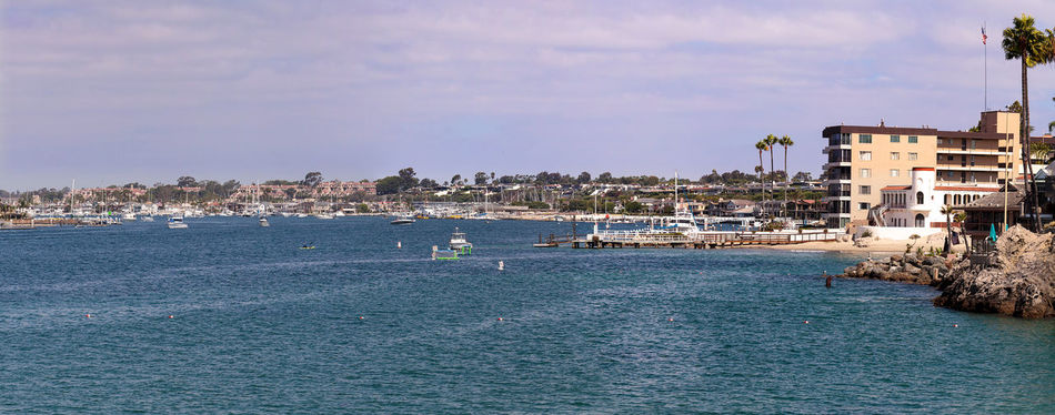 Corona del Mar harbor panoramic view from the rocks in summer Architecture Beach Building Exterior Built Structure California City Cityscape Corona Del Mar Day Harbor No People Ocean Outdoors Palm Tree Panoramic Sand Sea Sky Travel Destinations United States Water