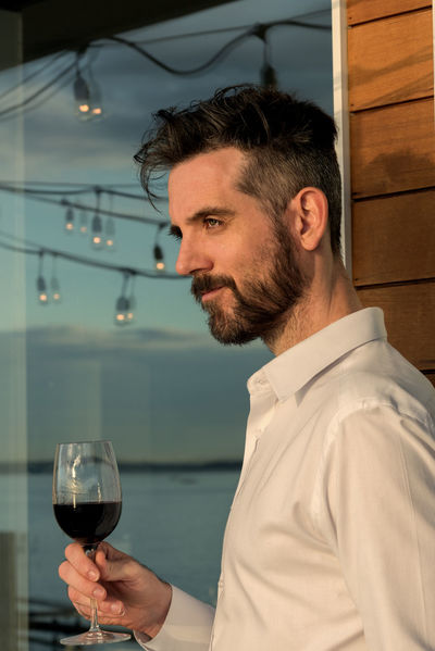 Handsome bearded man holding a glass of red wine gazing out to sea from a beach house deck. Beach House Entertaining Mens Health Alcohol Beard Close-up Day Deck Drink Grooming Hanging Lights Holding Indoors  Lifestye Lifestyles Luxury Masculine One Person Real People Smiling Wine Wineglass Winetasting Wood Siding Young Adult