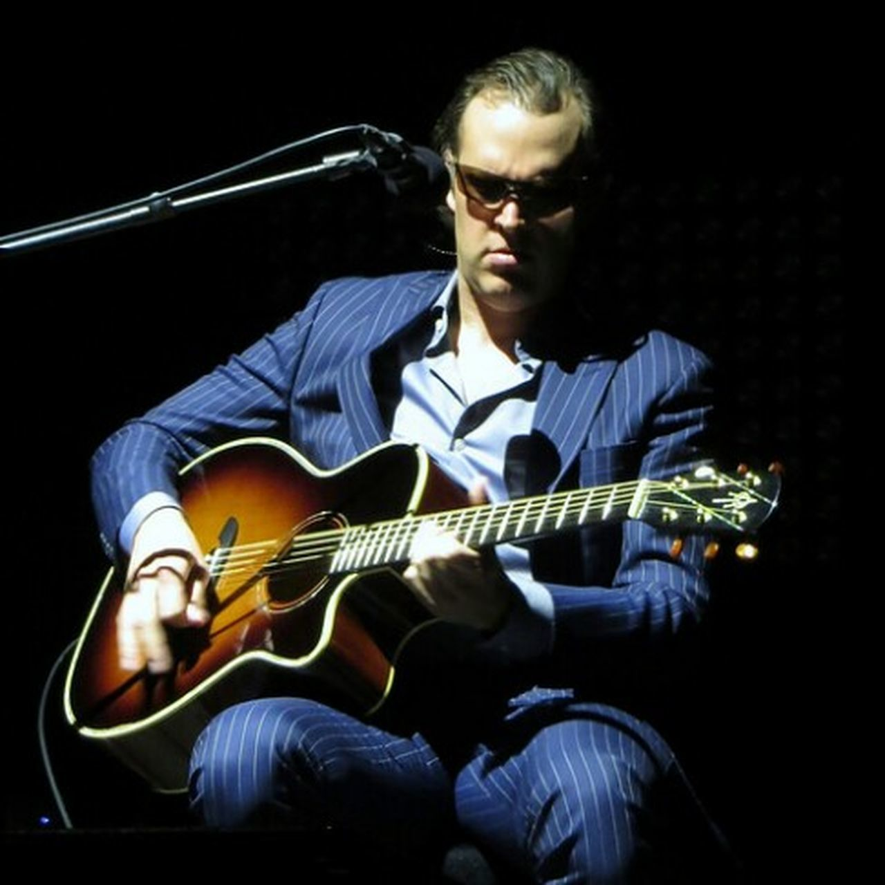 music, guitar, one man only, sunglasses, only men, sitting, musical instrument, plucking an instrument, black background, one person, adults only, young adult, adult, one young man only, musician, playing, casual clothing, people, men, studio shot, night, performance, eyeglasses, illuminated, indoors