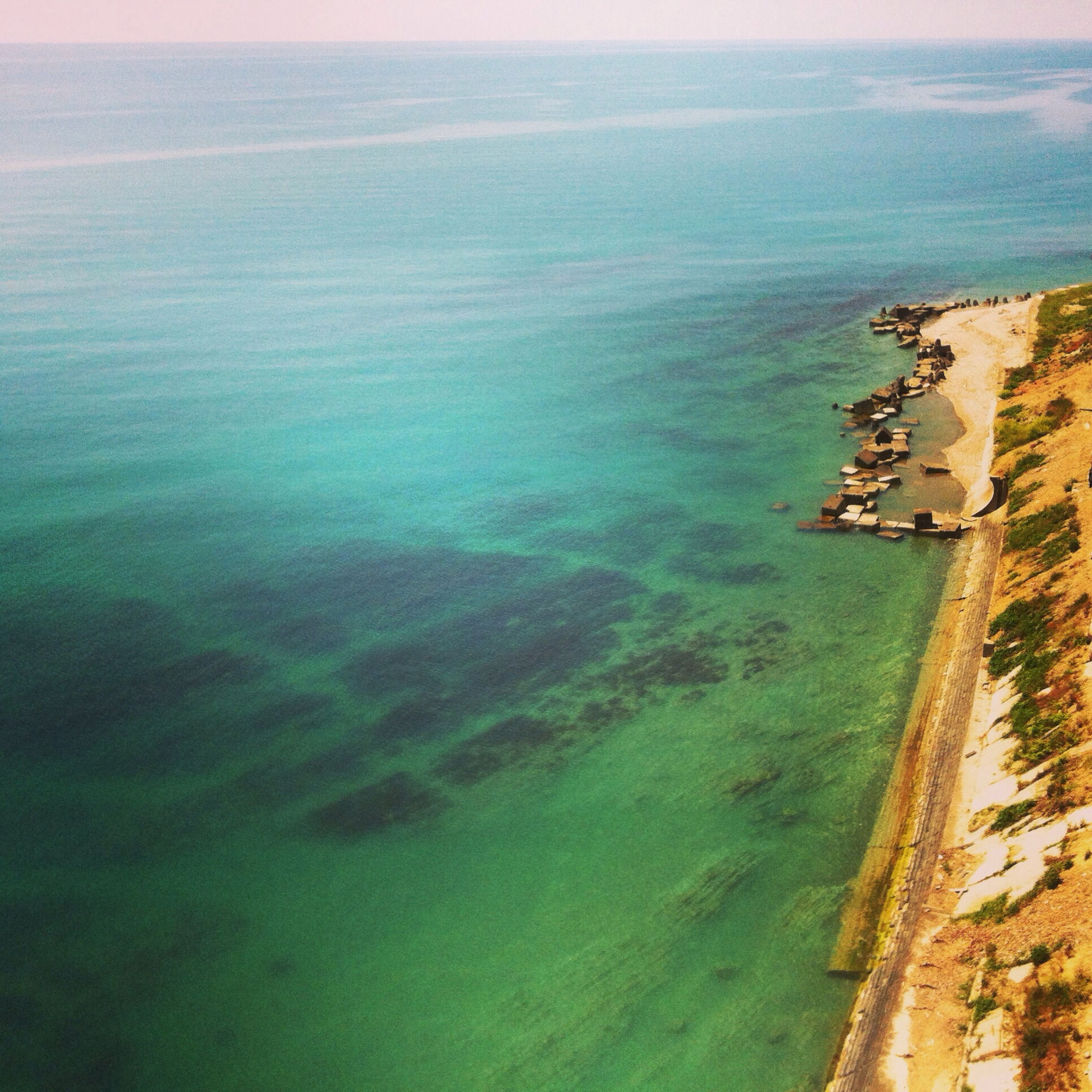 sea, water, horizon over water, high angle view, scenics, tranquil scene, tranquility, blue, beauty in nature, coastline, nature, built structure, architecture, seascape, idyllic, building exterior, beach, sky, ocean, shore