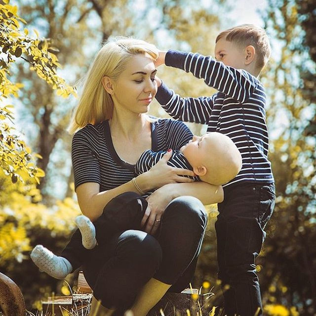 family with one child, adult, family, males, blond hair, togetherness, son, mother, people, child, mid adult, baby, parent, casual clothing, father, happiness, females, tree, love, sitting, outdoors, bonding, childhood, autumn, daughter, men, day, holding, full length, women, young adult, nature, sky