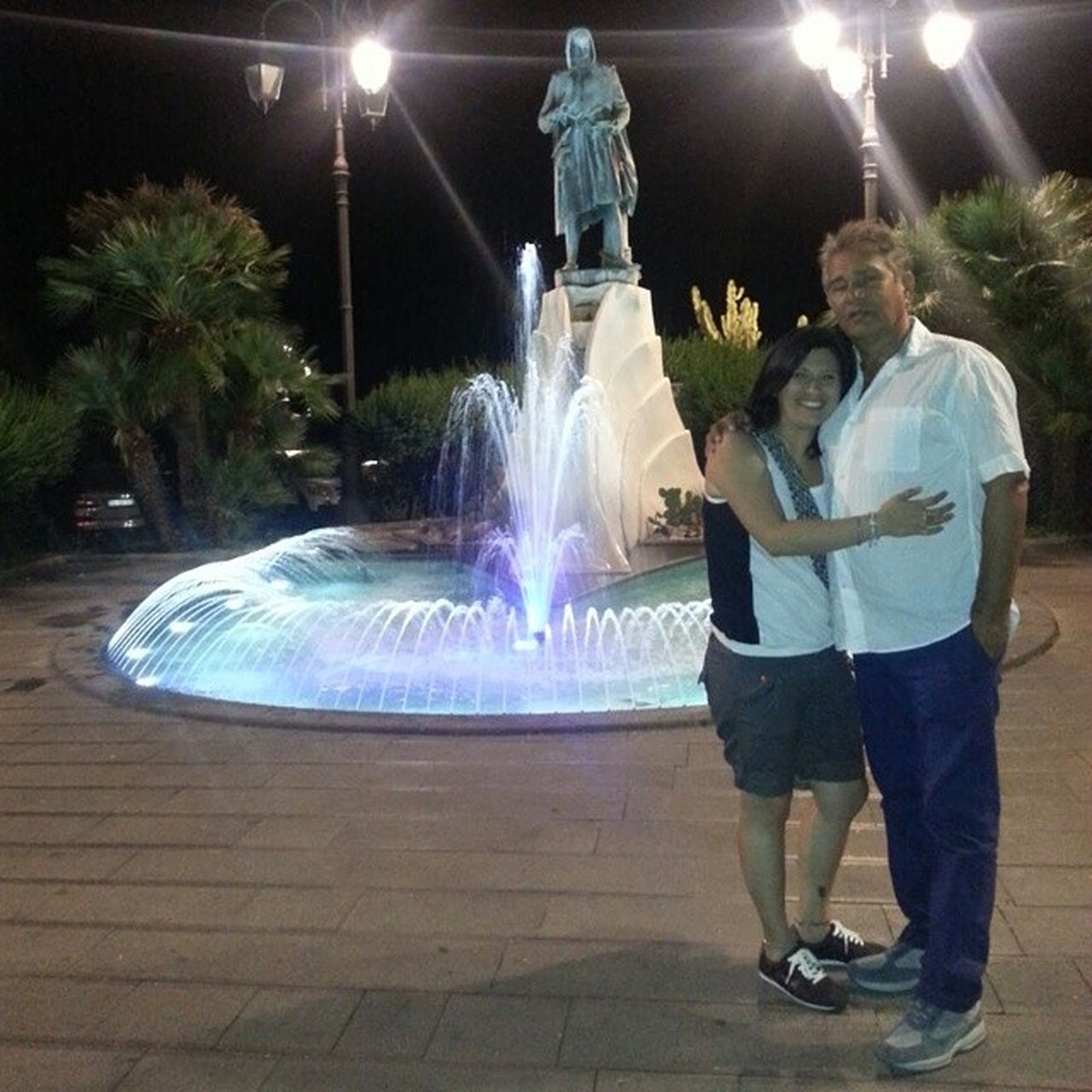 night, illuminated, lifestyles, leisure activity, full length, motion, men, long exposure, fountain, casual clothing, standing, rear view, street, spraying, arts culture and entertainment, person, lighting equipment, celebration