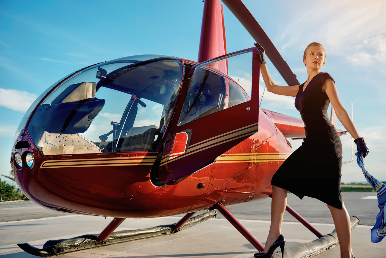 Elegant business woman flying away by the helicopter. Business, success and luxury concept Aircraft Airport Blond Hair Businesswoman Career Elegant Females Full Length Helicopter Landing Field Lifestyles Luxury Mode Of Transport One Person Outdoors Private Plane Representative Rich Sky Success Successful Sunny Day Transportation Young Adult Young Women