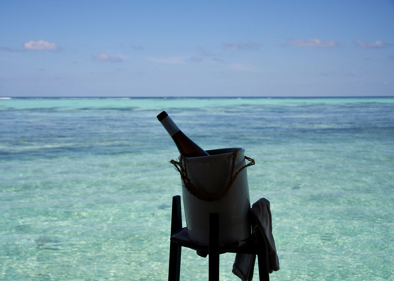 Wine Bottle in Container in front of Blue Sea Horizon Backgrounds Beach Blue Bottle Colors Container Drink Food And Drink Health Holiday Horizon Over Water Maldives Nature Life Outdoors Refreshment Scenics Sea Sky Tranquil Scene Tropical Climate Turquoise Water Wine Light