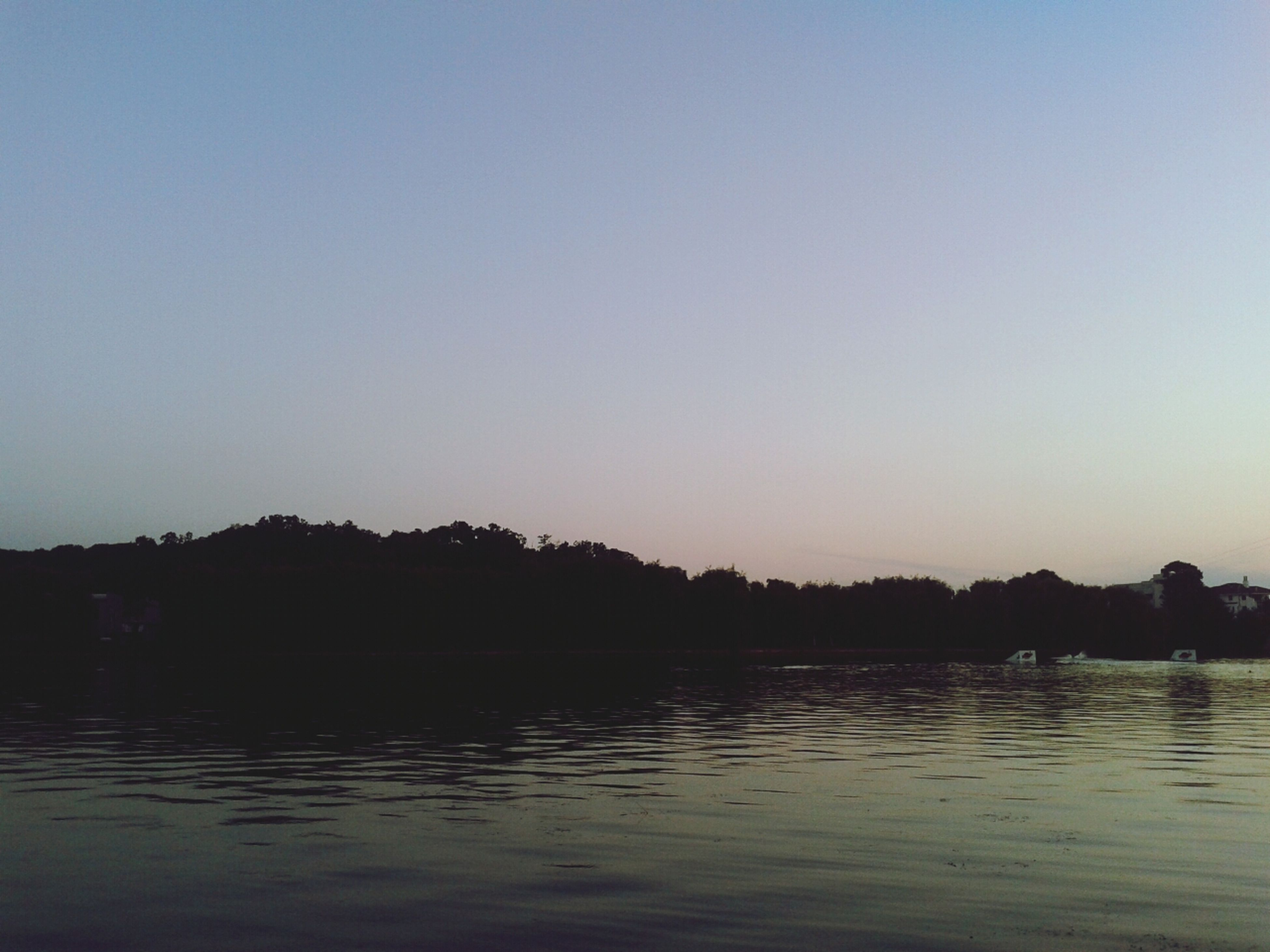 water, clear sky, copy space, waterfront, silhouette, tranquil scene, tranquility, scenics, sunset, lake, reflection, beauty in nature, nature, tree, idyllic, river, dusk, calm, outdoors, sky