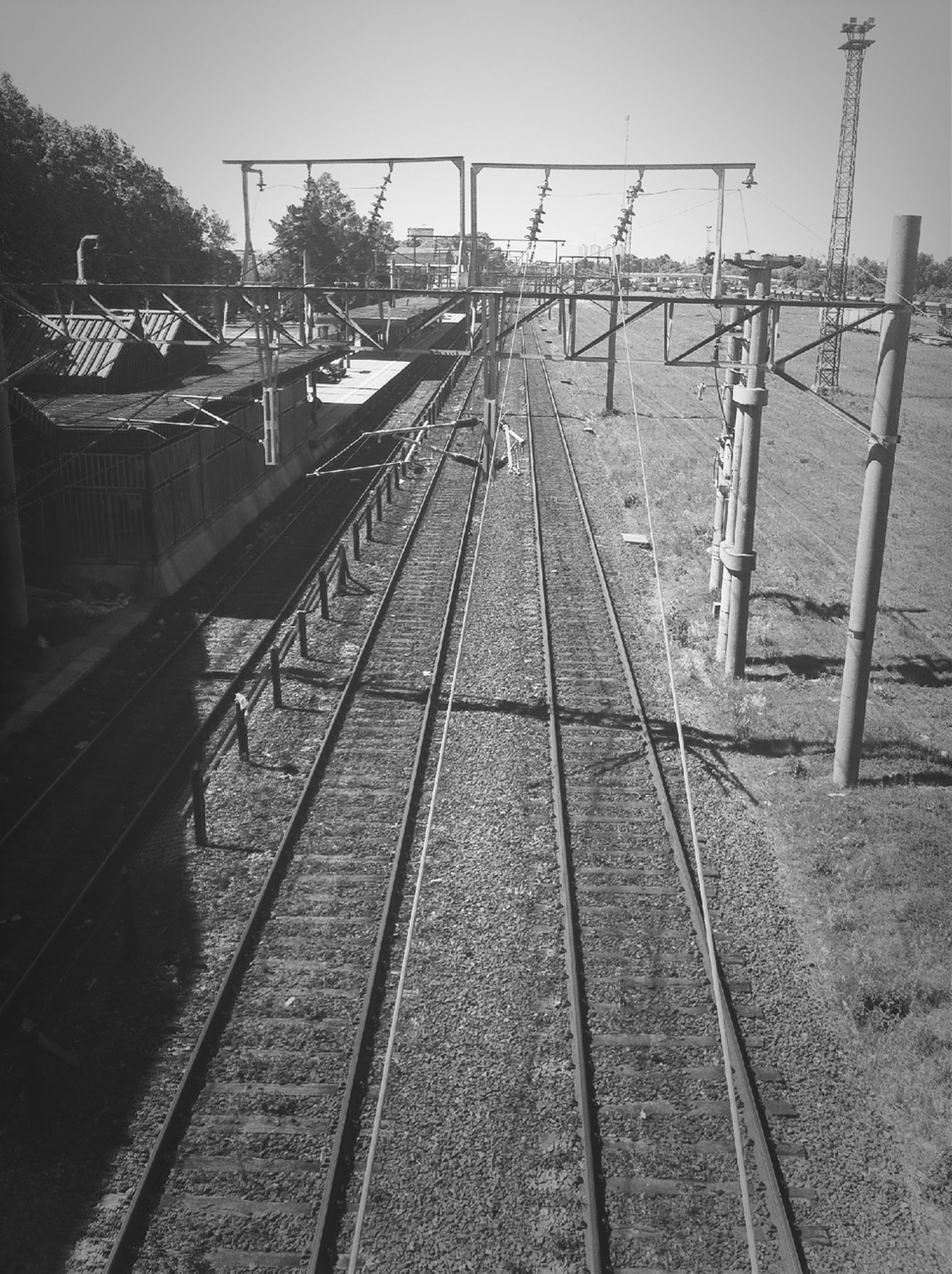railroad track, transportation, rail transportation, clear sky, public transportation, built structure, the way forward, sky, railroad station, railroad station platform, mode of transport, day, metal, outdoors, architecture, diminishing perspective, sunlight, vanishing point, connection, no people