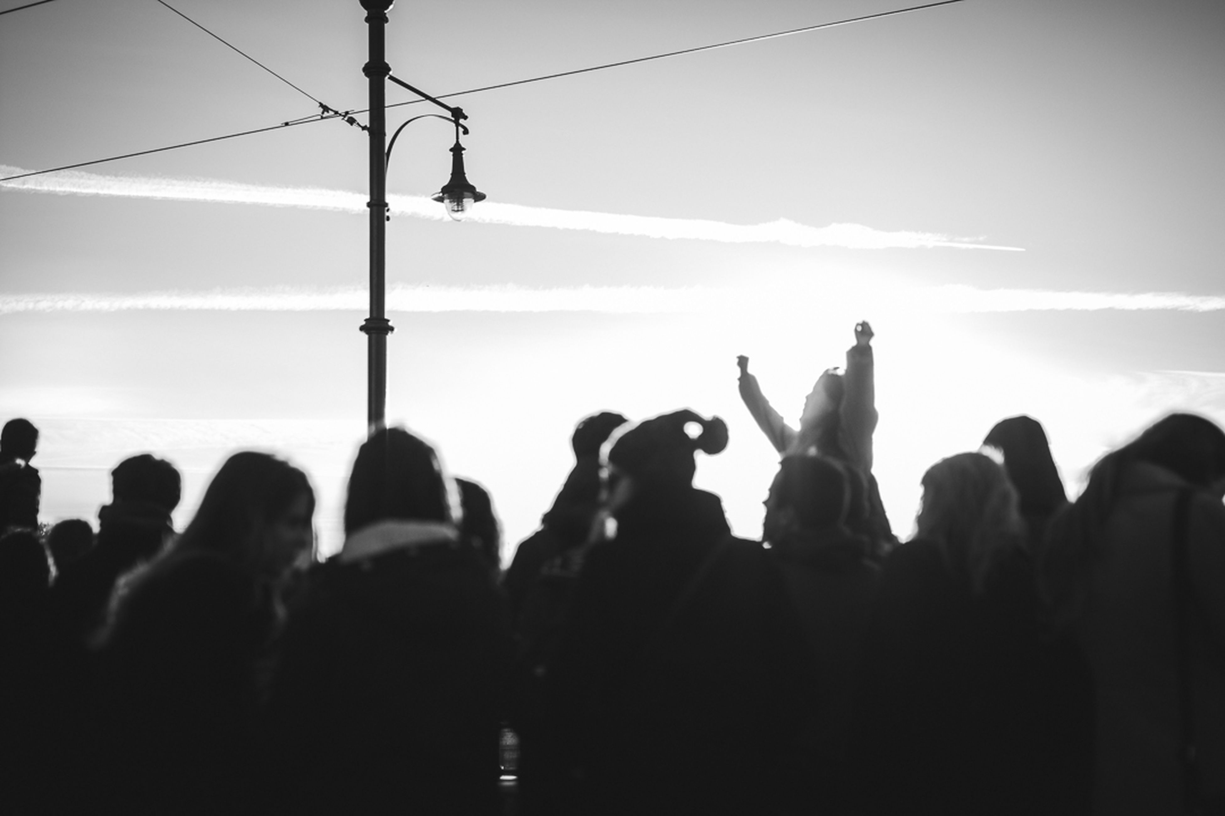 silhouette, men, large group of people, lifestyles, person, leisure activity, sky, togetherness, crowd, performance, standing, enjoyment, sunset, outline, outdoors, medium group of people, technology, arts culture and entertainment