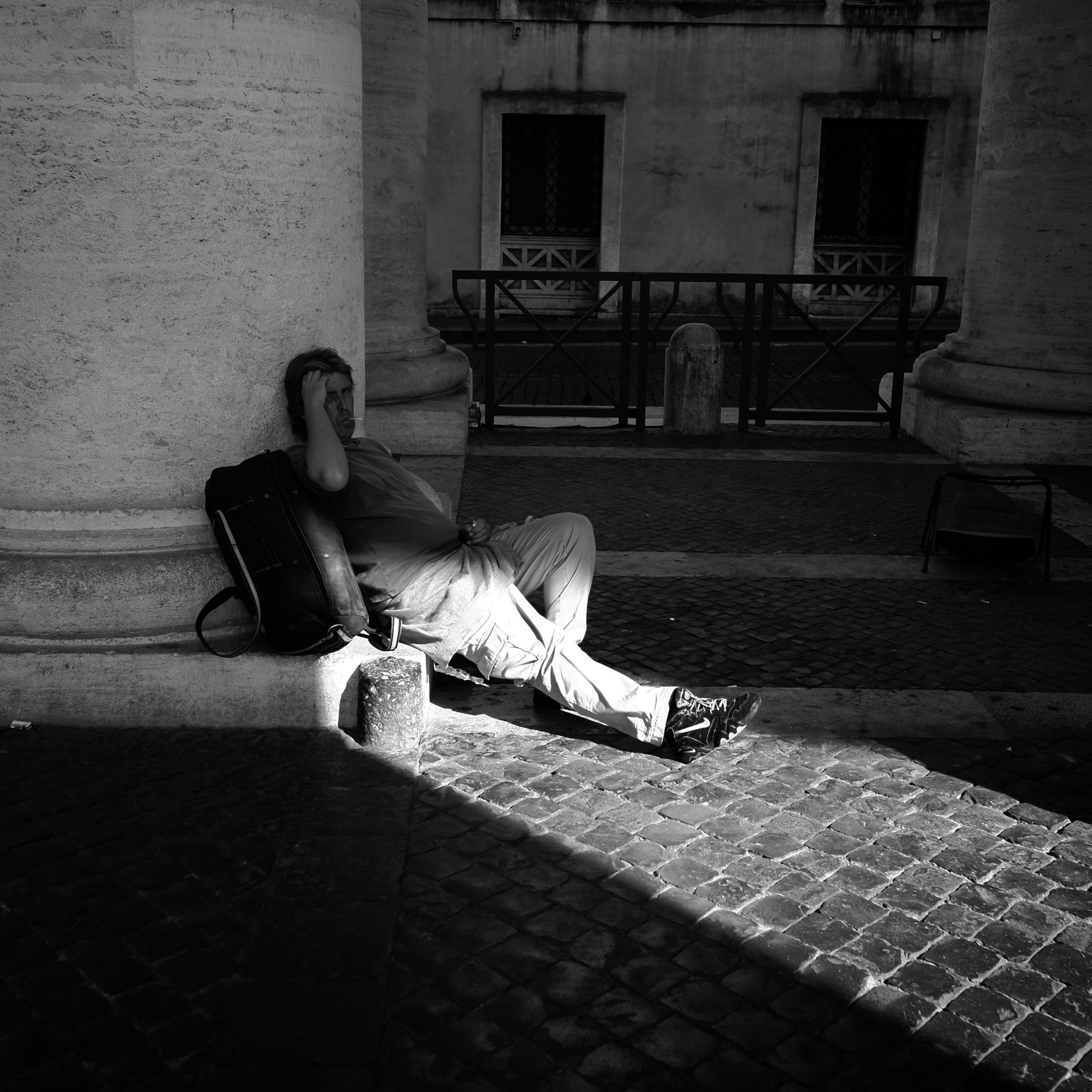 full length, building exterior, architecture, built structure, lifestyles, side view, street, leisure activity, sitting, casual clothing, sidewalk, cobblestone, childhood, shadow, outdoors, day, chair, sunlight