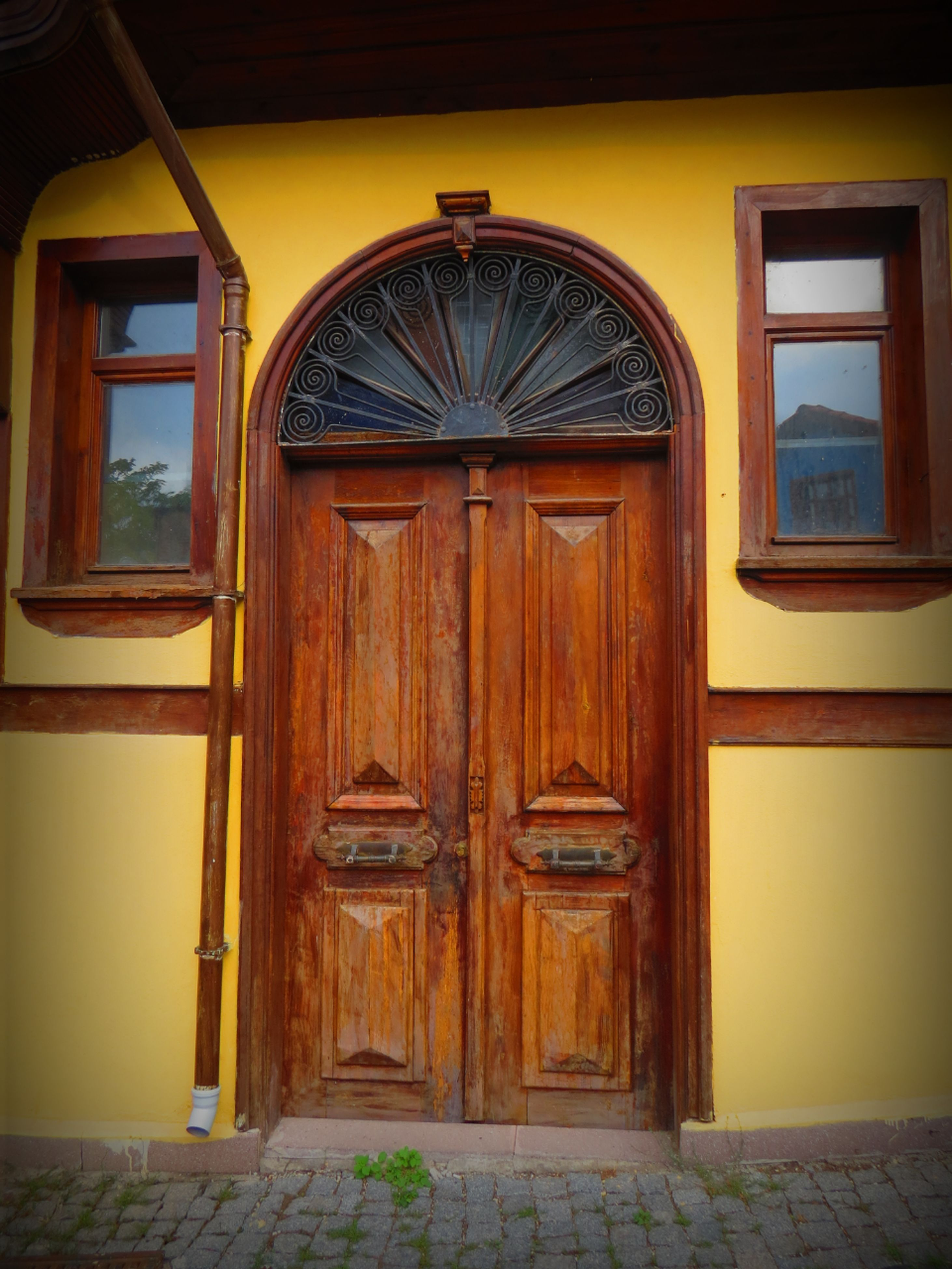 door, closed, architecture, built structure, entrance, building exterior, window, house, wood - material, safety, yellow, doorway, arch, open, protection, no people, security, empty, absence, gate