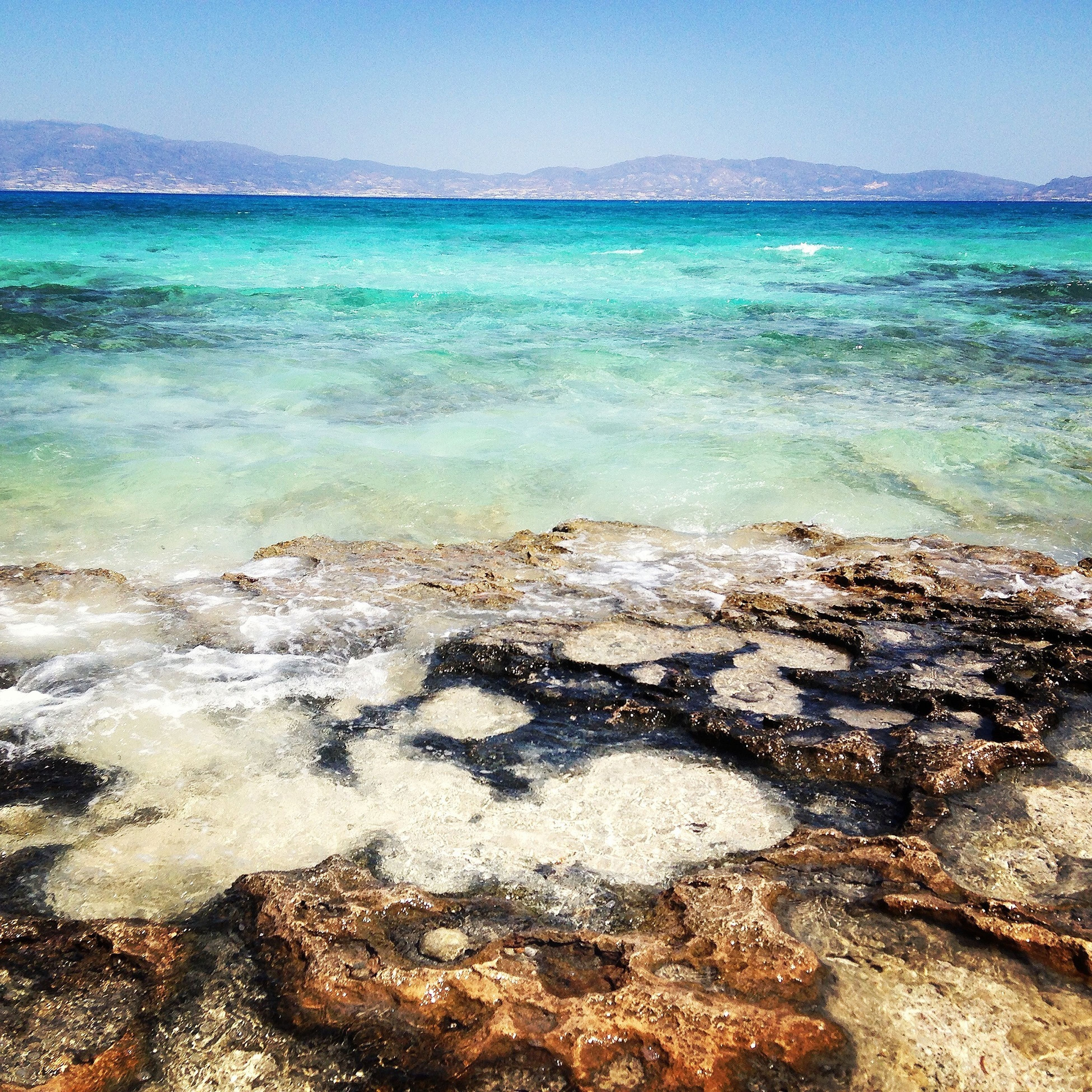 water, sea, beach, shore, tranquil scene, scenics, tranquility, beauty in nature, blue, horizon over water, wave, nature, surf, sky, sand, idyllic, clear sky, rock - object, coastline, outdoors