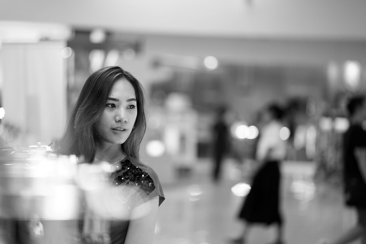 Thoughtful Woman Looking Away While Standing At Shopping Mall