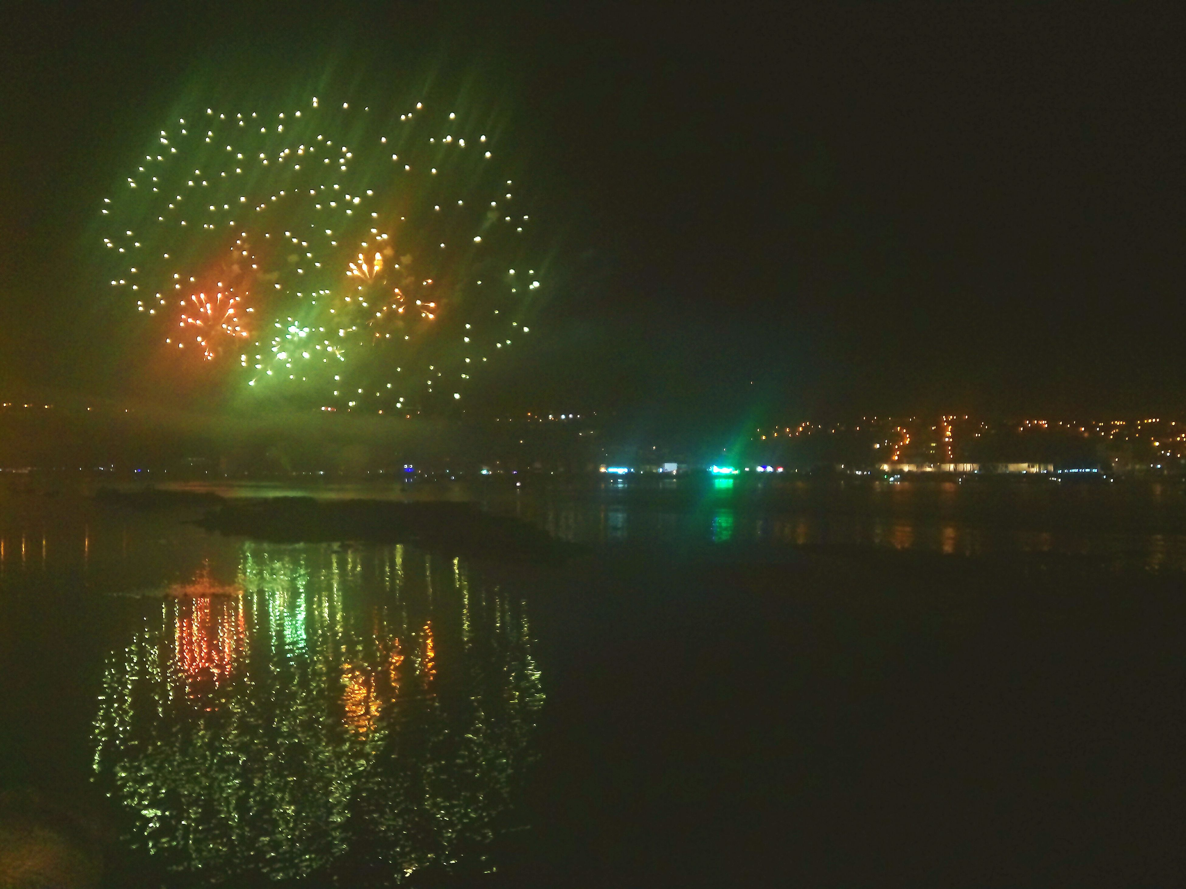 night, illuminated, building exterior, water, architecture, built structure, reflection, city, firework display, glowing, waterfront, river, celebration, sky, long exposure, exploding, cityscape, firework - man made object, clear sky, light