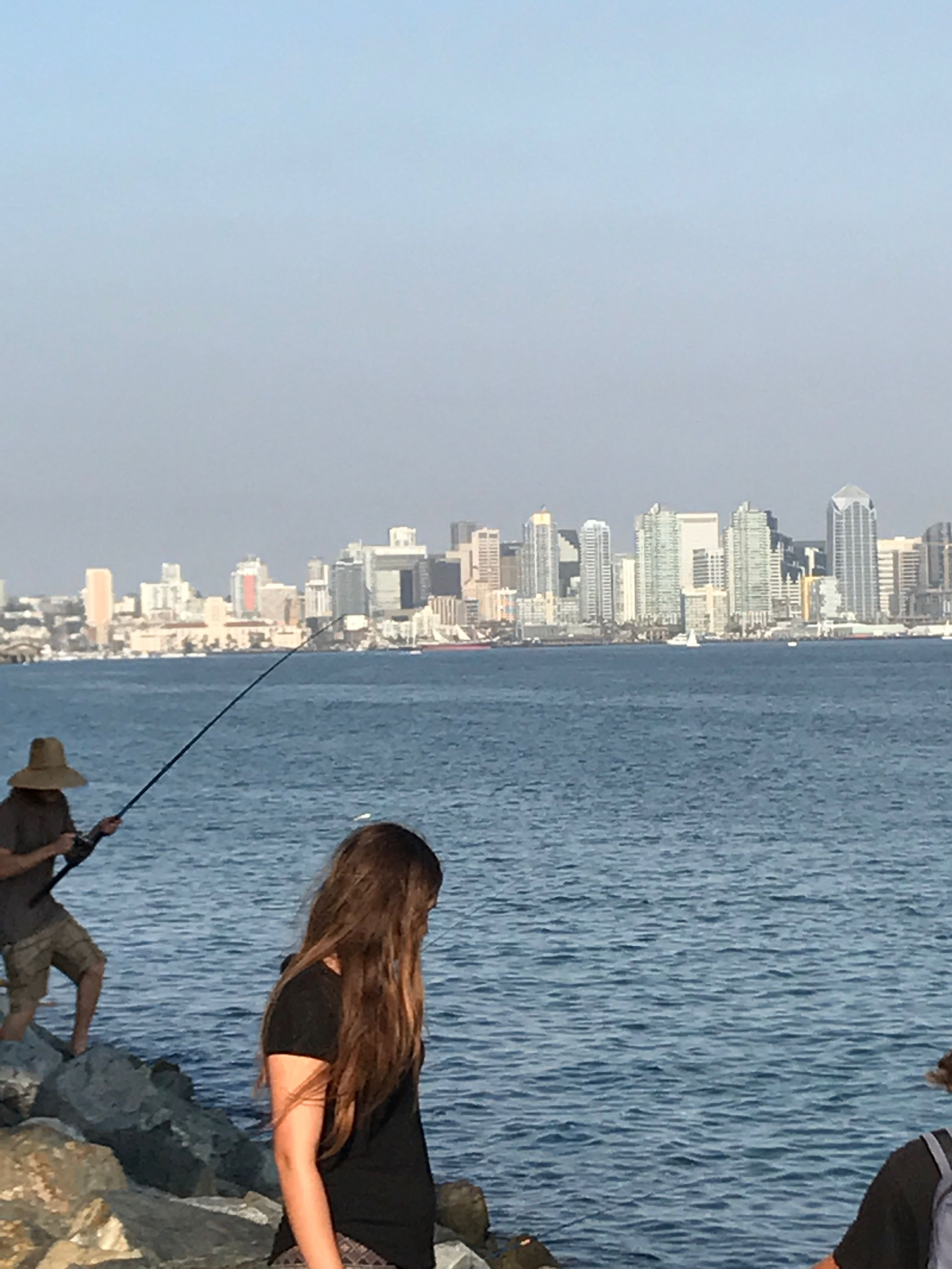 sea, real people, skyscraper, water, architecture, rear view, leisure activity, one person, built structure, building exterior, standing, city, day, lifestyles, clear sky, nature, outdoors, cityscape, scenics, horizon over water, urban skyline, sky, women, full length, beauty in nature, young adult, people