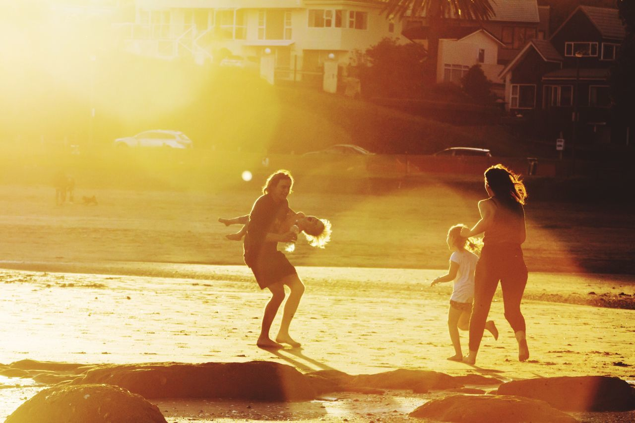 sunlight, beach, full length, real people, lens flare, togetherness, sea, leisure activity, sand, fun, outdoors, enjoyment, vacations, childhood, water, boys, lifestyles, nature, girls, building exterior, playing, standing, men, day, adult, people