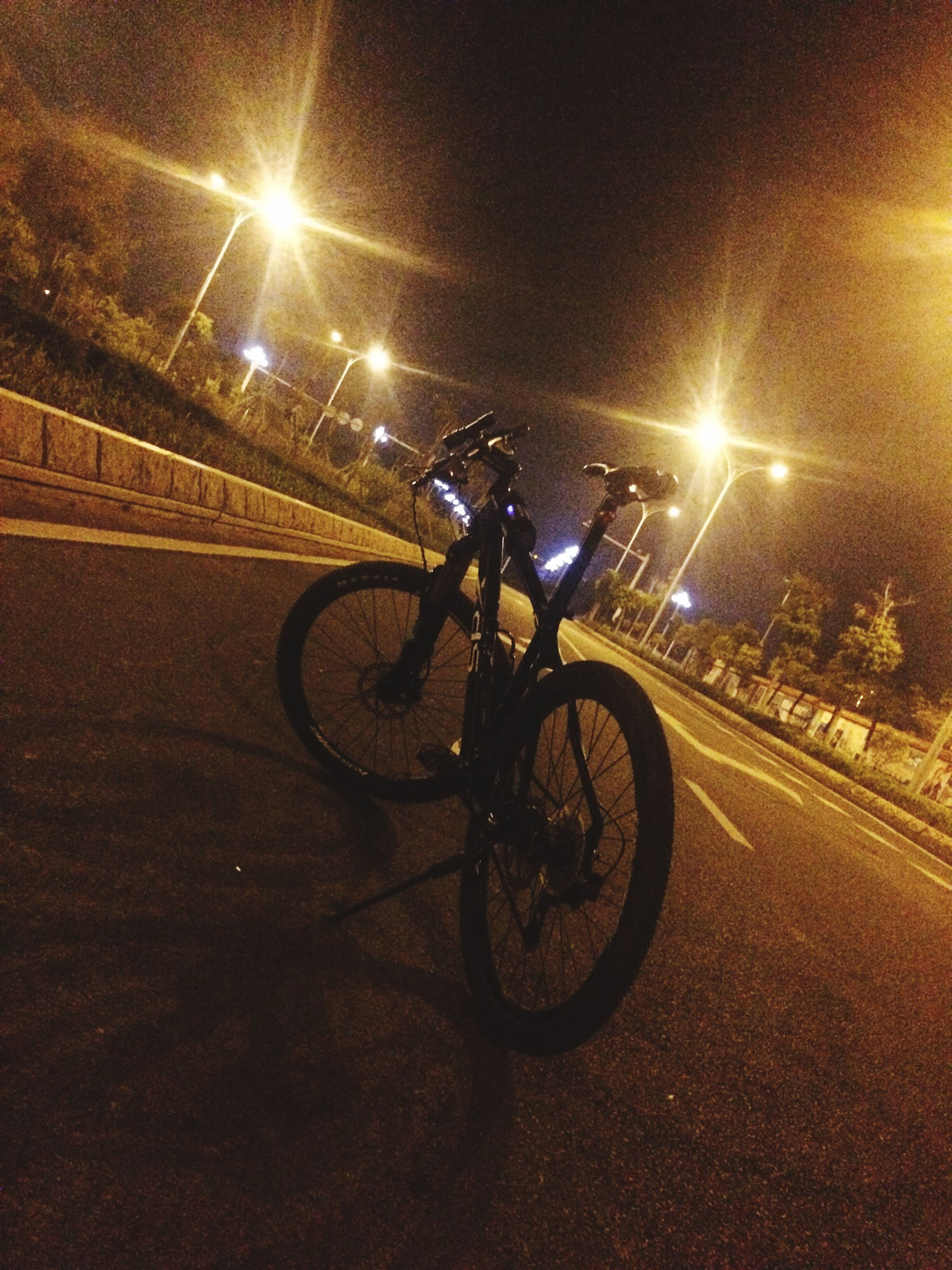 transportation, illuminated, mode of transport, night, land vehicle, bicycle, street, road, street light, lighting equipment, built structure, on the move, stationary, car, architecture, parking, motion, road marking, parked, the way forward