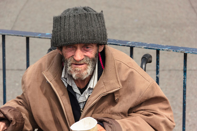 Old man in wheelchair begging with a crumpled up papper cup wearing a large overcoat and dark green woolen hat. Beard Bearded Begging Close-up Cup Dark Green Day Homeless No Other People Old Man One Man Only One Person Outdoors Portrait Railing Real People Retirement Senior Adult Social Issues Street People Street Portrait Thin Warm Clothing Wheelchair Wool Hat