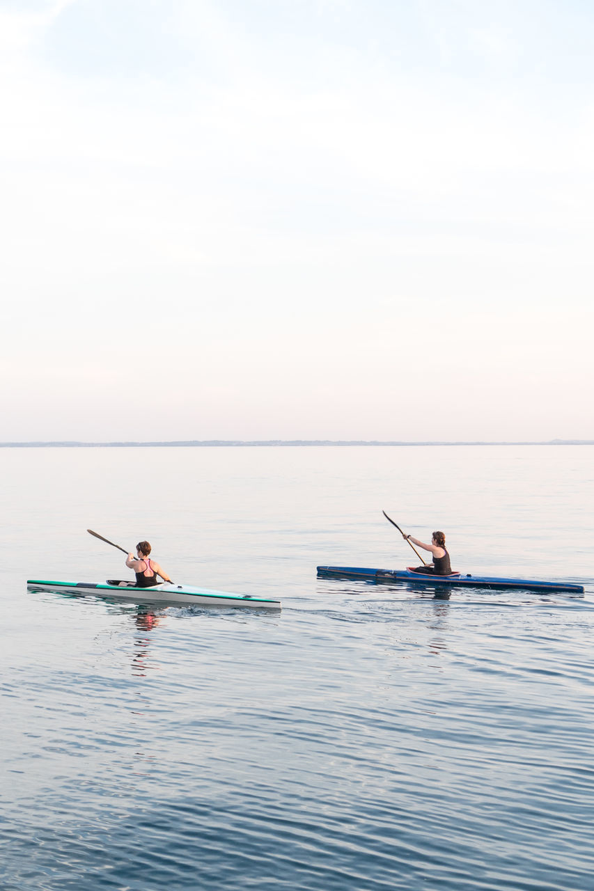 two people, sea, water, nature, rear view, tranquility, outdoors, men, day, oar, scenics, sitting, horizon over water, rowing, beauty in nature, sky, togetherness, full length, teamwork, adult, sportsman, young adult, adults only, people