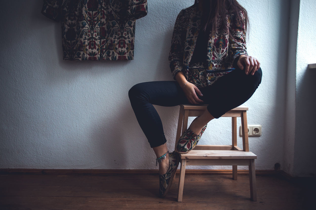 She is looking for matching pants.. Chair Day Hardwood Floor Home Interior Human Leg Indoors  Natural Light One Person One Woman Only Sitting Wall