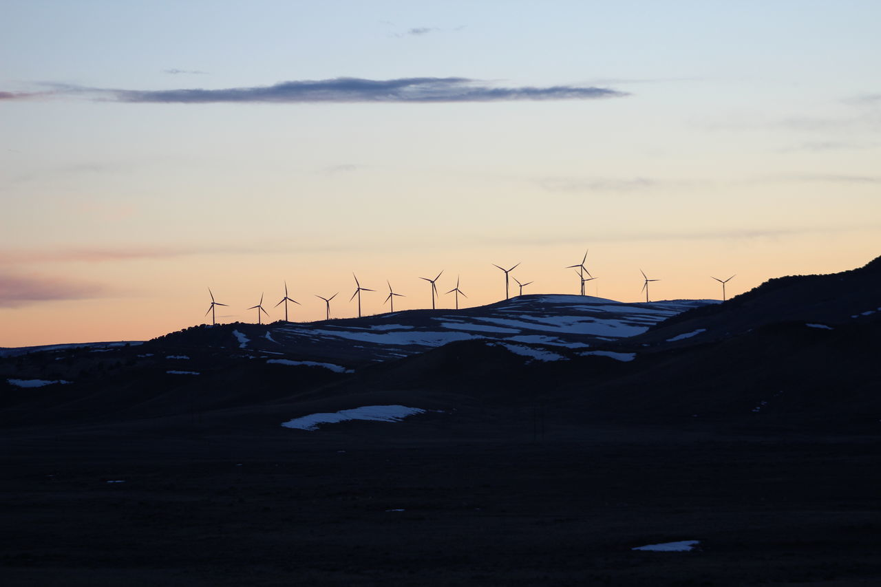 Silhouette windmills on mountain at sunset