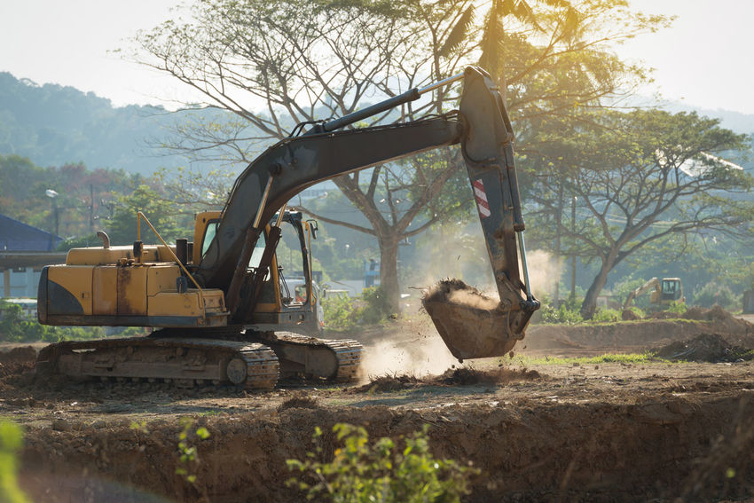 Construction site area. Building - Activity Construction Machinery Construction Site Construction Worker Day Digging Earth Mover Excavator Industry Machinery Men One Person Outdoors People Real People Sky Tree Working