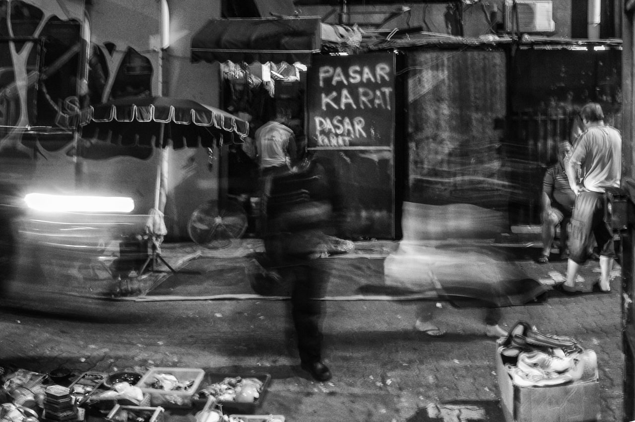 Pasar Karat (Flea market) in the early hours whereby the sellers trying to arrange their products in a limited light Black & White Black And White Blackandwhite Flea Markets Fleamarket Illuminated Kuala Lumpur Kuala Lumpur Malaysia  Light Trail Long Exposure Men Motion Blur Night Night Photography Outdoors Pasar Karat Petaling Street Real Life Real People Slow Shutter