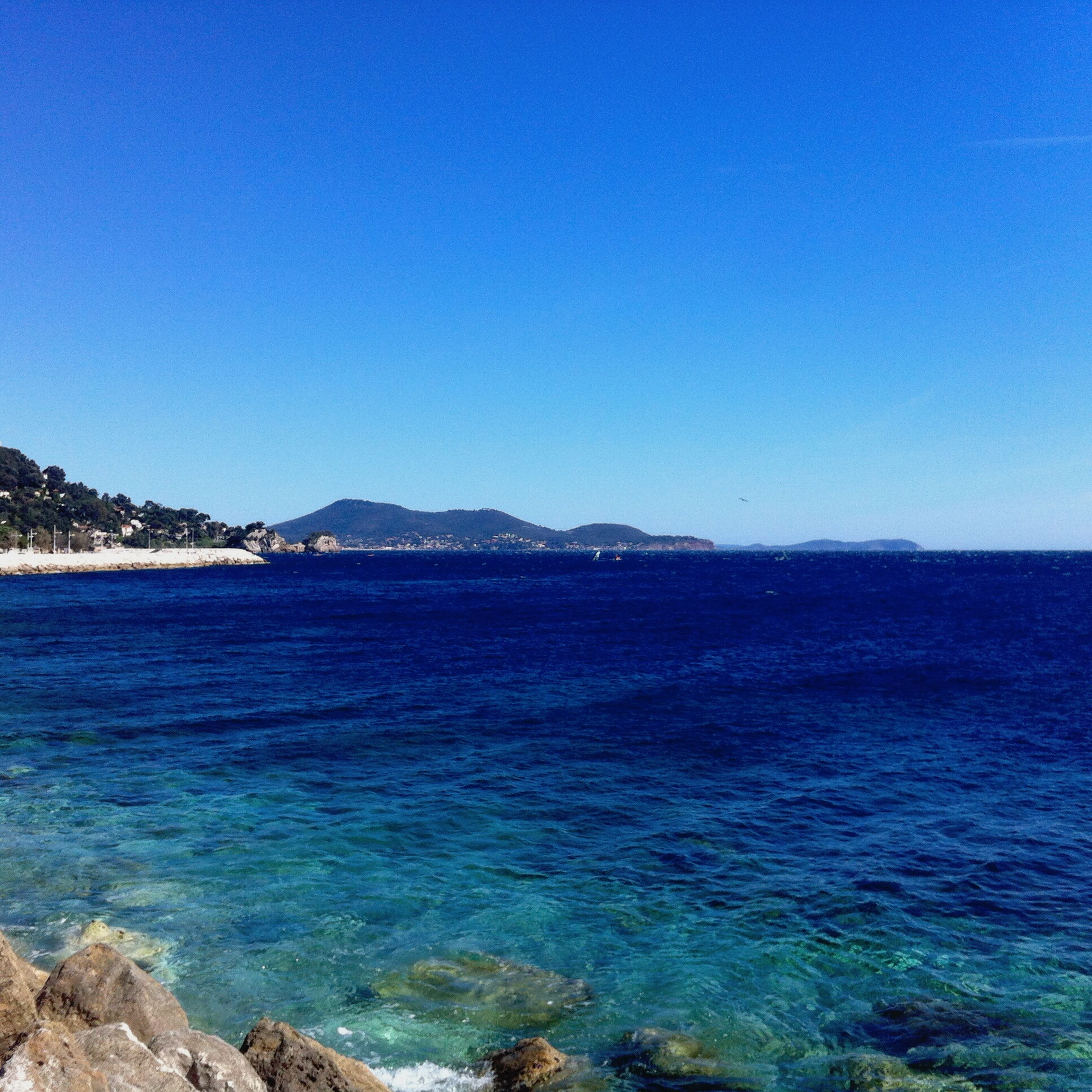 blue, clear sky, copy space, water, sea, scenics, tranquil scene, beauty in nature, tranquility, nature, mountain, idyllic, horizon over water, rock - object, day, waterfront, coastline, rippled, outdoors, built structure
