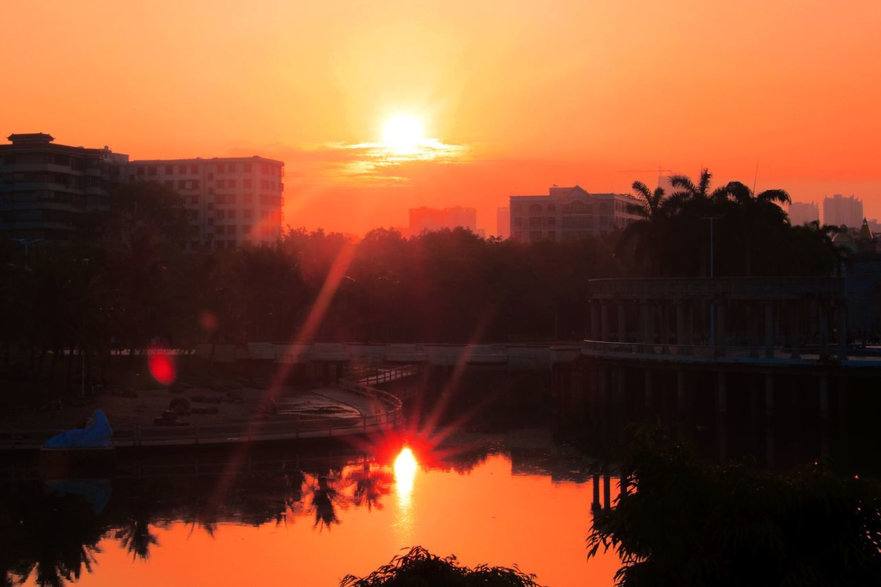 sunset, reflection, sun, orange color, water, building exterior, tree, architecture, built structure, silhouette, sunlight, sky, outdoors, nature, waterfront, beauty in nature, no people, lake, scenics, city, day