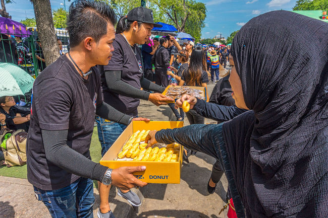 A young man hands out free doughnuts as rowds wait to sing the Royal Anthem in honour of HM King Bhumibol Adulyadej. Adult Bangkok Bangkok Thailand. City Day Horizontal King Bhumipol Adulyadet Outdoors People Person Volunteer Volunterering Young Adult